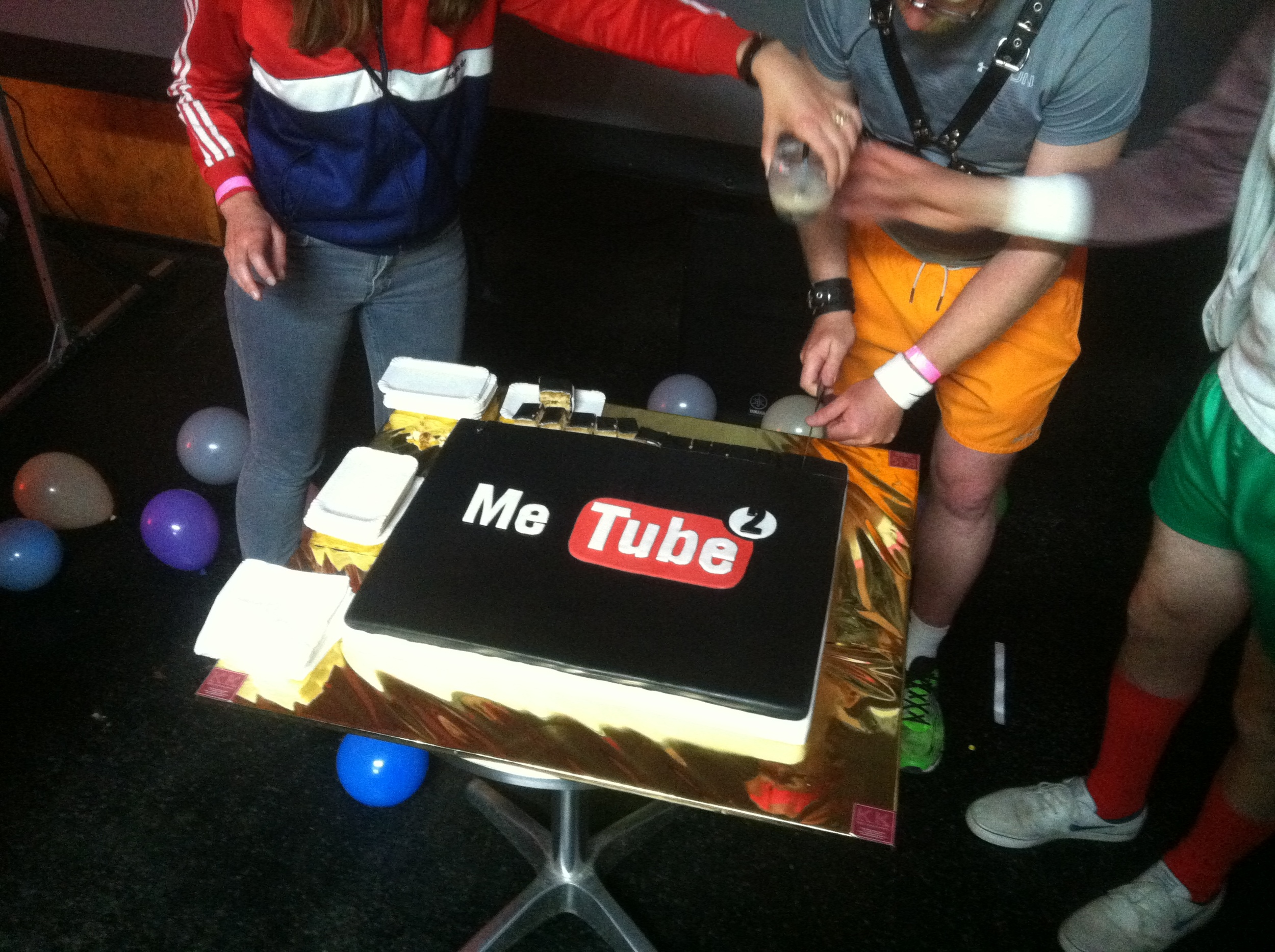 people in sport shorts cutting the official metube cake