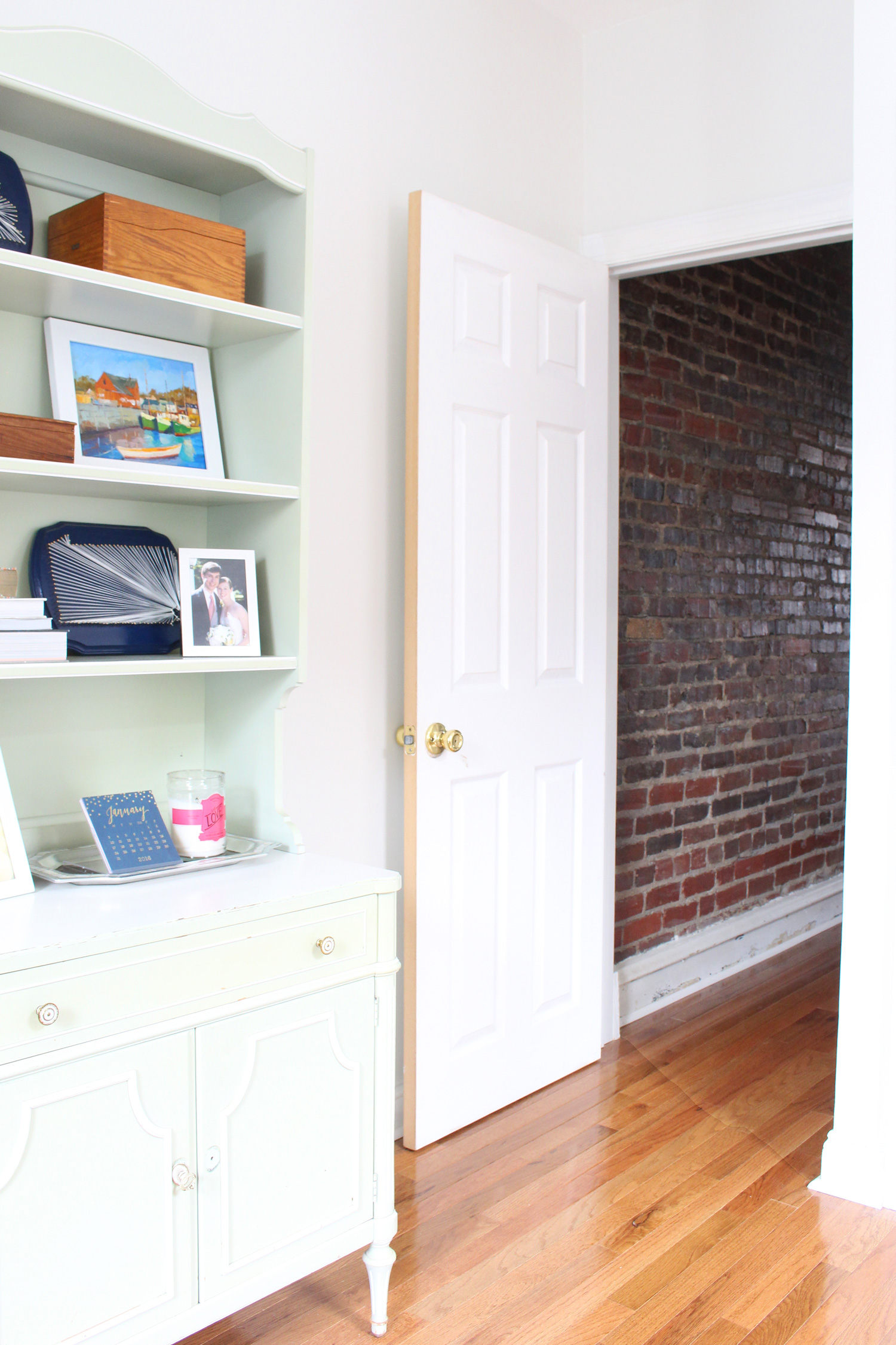 Door from the office to the exposed brick hallway.