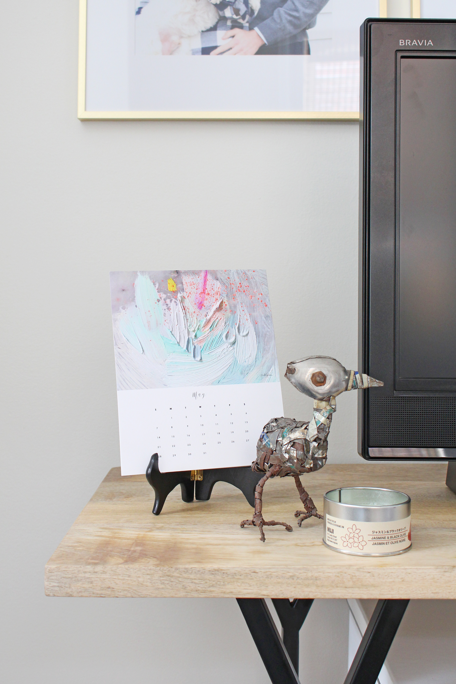 A calendar from Emily Jeffords, a funky metal bird, and a candle are great additions to this console table