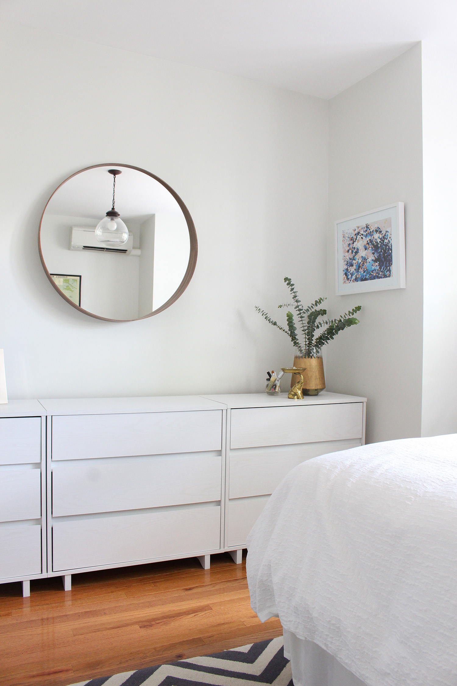 Art from Art Crate (Artist: Katie Craig) hangs over these modern, minimalist dressers.