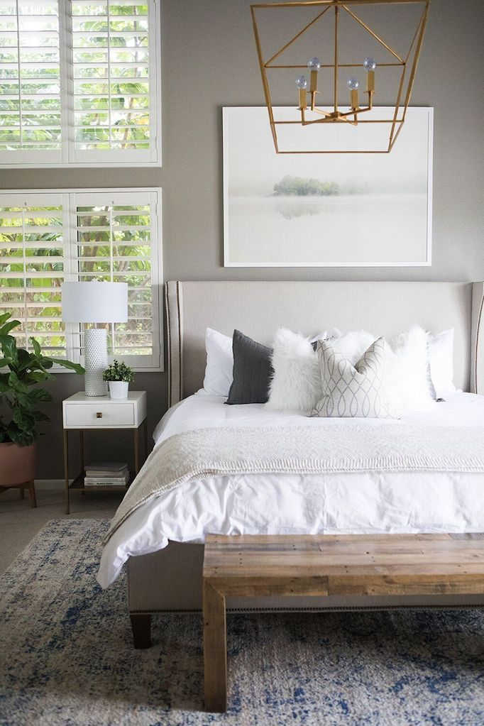 How to decorate around a bed. Option: hang a large piece of art on the wall above the bed. (Design: Becki Owens) // neutral bedroom, art above bed, upholstered bed, feminine bedroom.