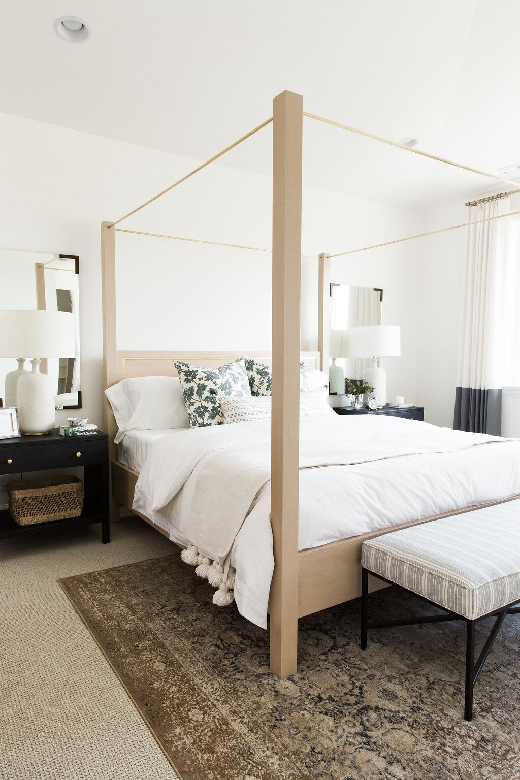 How to decorate around a bed. Option: Hang matching mirrors on either side of the bed above nightstands or bedside tables. (Design: Studio McGee) // neutral bedroom, mirrors above nightstands, white bedroom, transitional bedroom, modern traditional bedroom