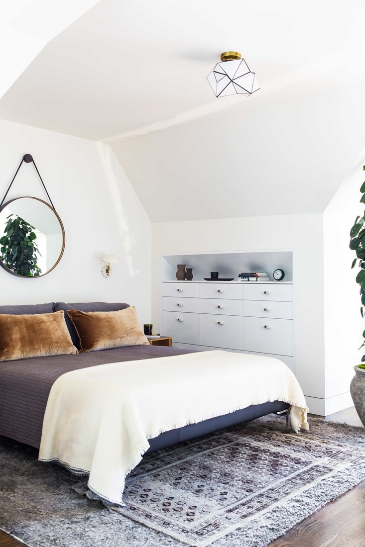 How to decorate around a bed. Option: Hang a mirror above the bed. (Design: Lauren Geremia via Architectural Digest) // gray bedroom, round mirror in bedroom, captain's mirror in bedroom, angled ceiling bedroom