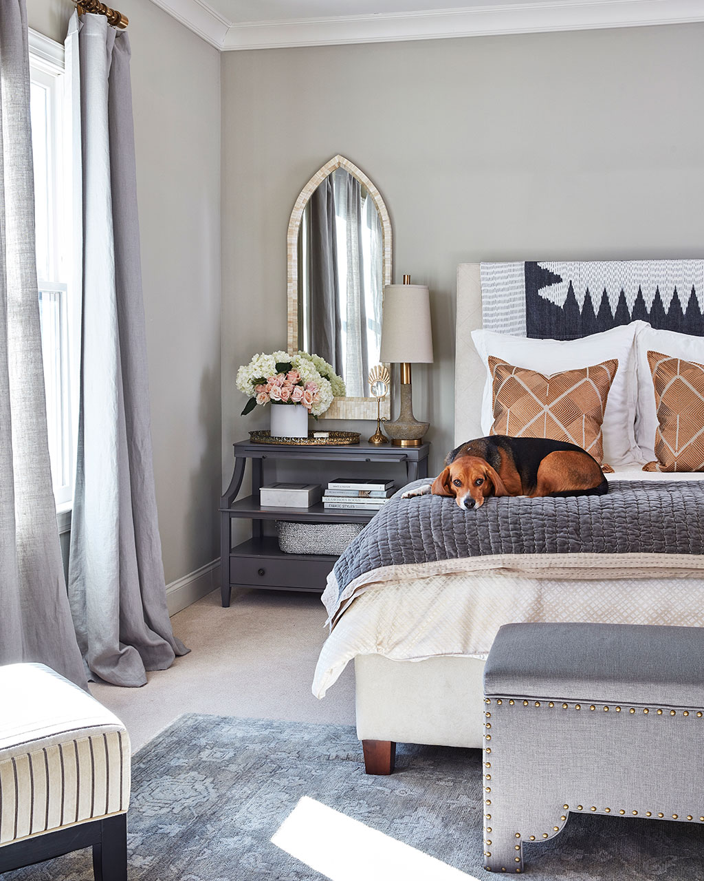 How to decorate around a bed. Option: hang mirrors above nightstands. (Design: Natalie Nasser via Ballard Designs) // mirrors above nightstands, mirrors above bedside tables, gray and white bedroom, traditional bedroom, transitional bedroom