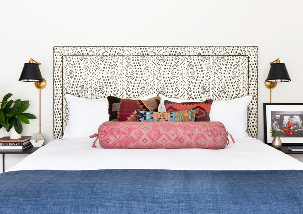 How to decorate around a bed: Leave the walls empty and let another element shine like this black and white patterned headboard. // animal print headboard, blue white pink bedroom, modern eclectic bedroom.
