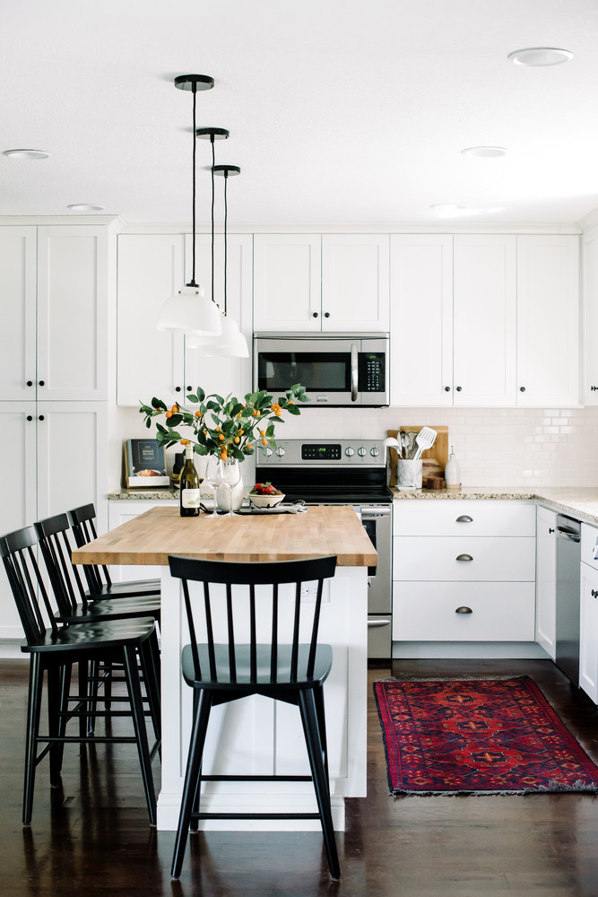 How to choose the right bar stools for your kitchen island or peninsula. // black windsor bar stools, white kitchen, vintage rug in kitchen