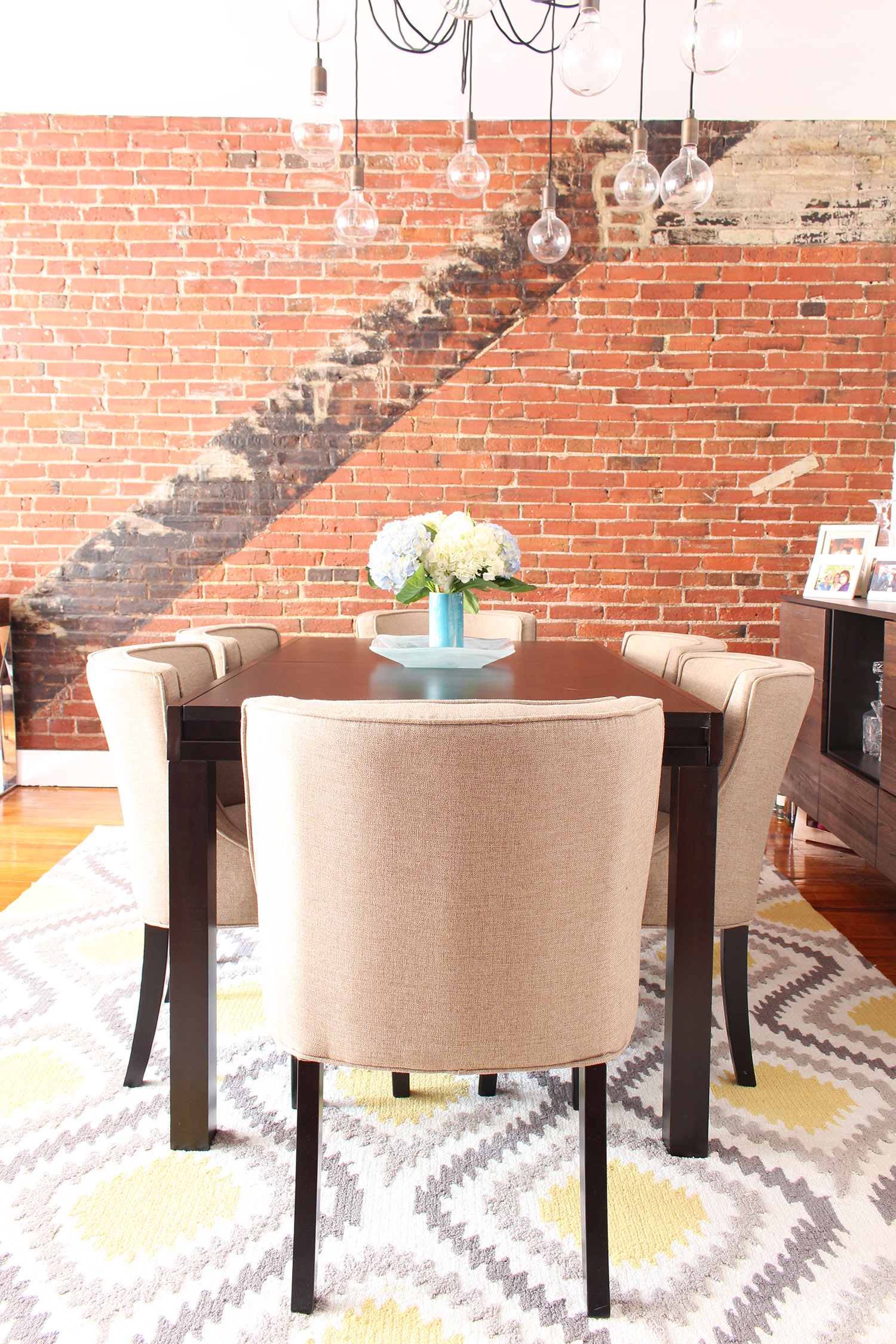 Contemporary meets classic in this converted textile factory condo's dining room in Philadelphia // contemporary dining room, transitional dining room, exposed brick