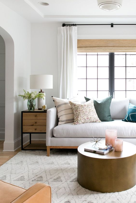 Hang curtains higher and wider than the window frame to help a room feel larger. Get other small space tips over on the Mix & Match Blog. (Design: Studio Mcgee)