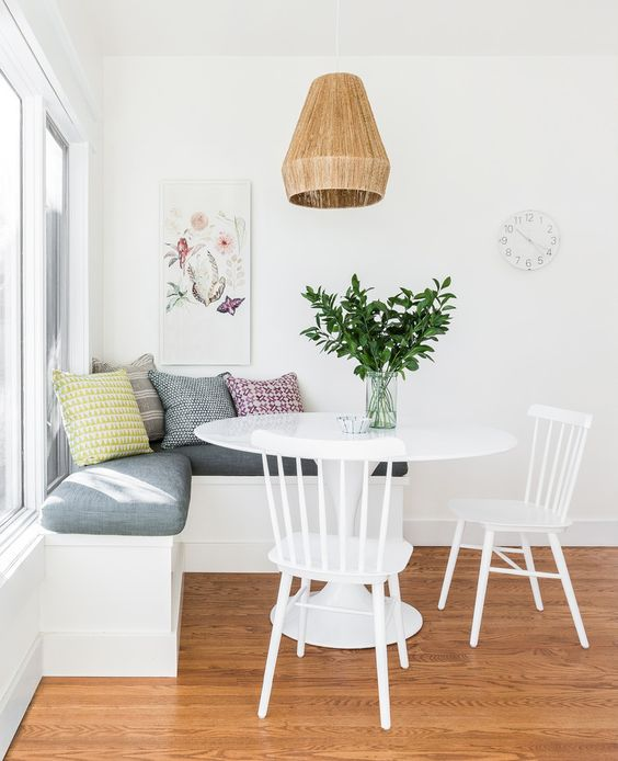 Small breakfast nook feels open and airy with white walls and furniture. Get more small space decorating tips at the Mix & Match Blog!