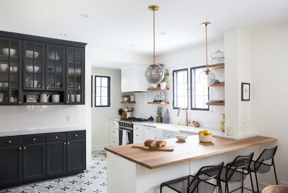 A mix of butcher block and quartz countertops in this kitchen. Learn how and when to mix countertop materials in this blog post! // white and black kitchen