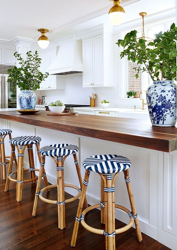 White quartz and thick butcher block countertops make this kitchen special and unique. Mix countertop materials in a kitchen.