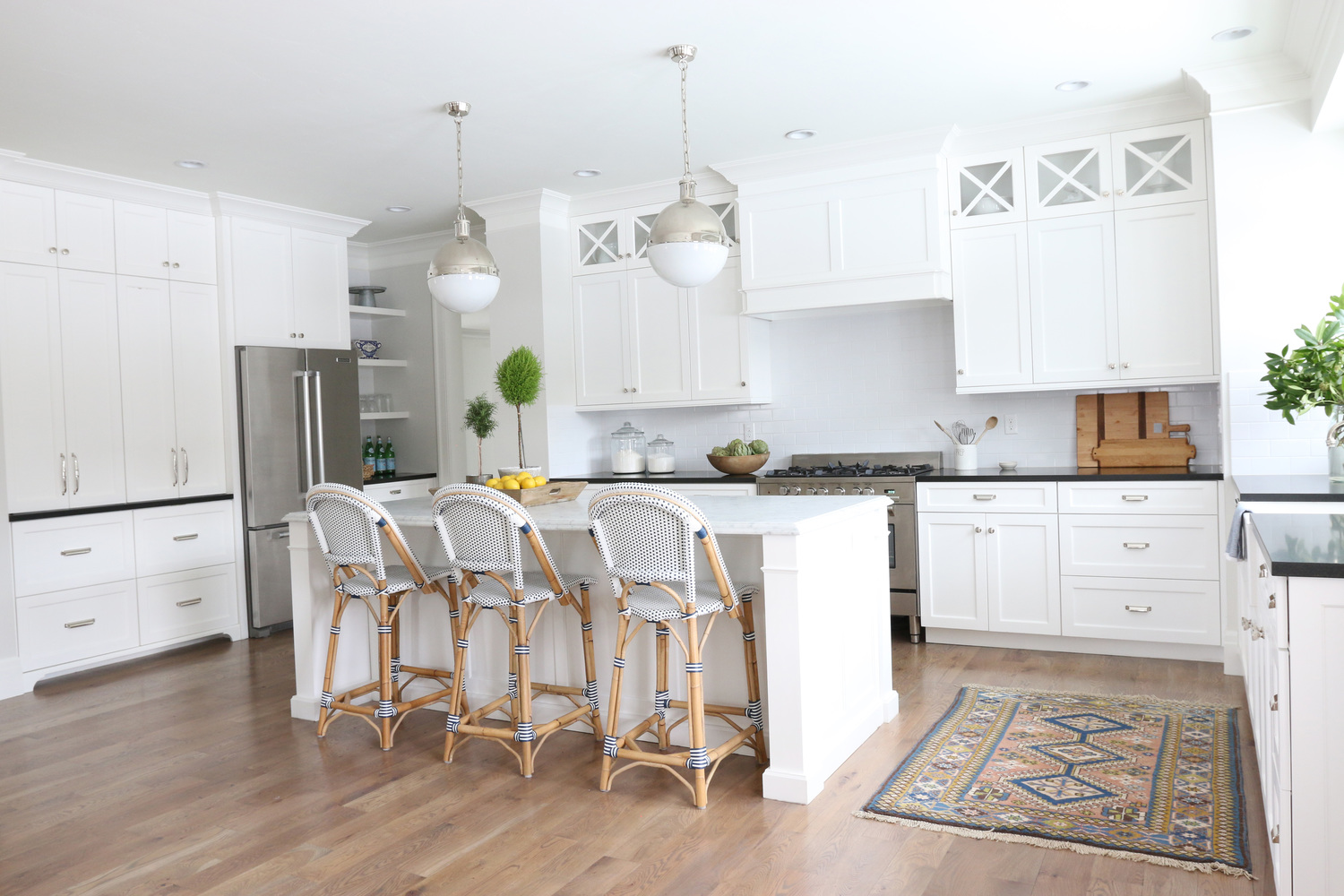 White kitchen with marble island and black countertops on perimeter. Studio McGee