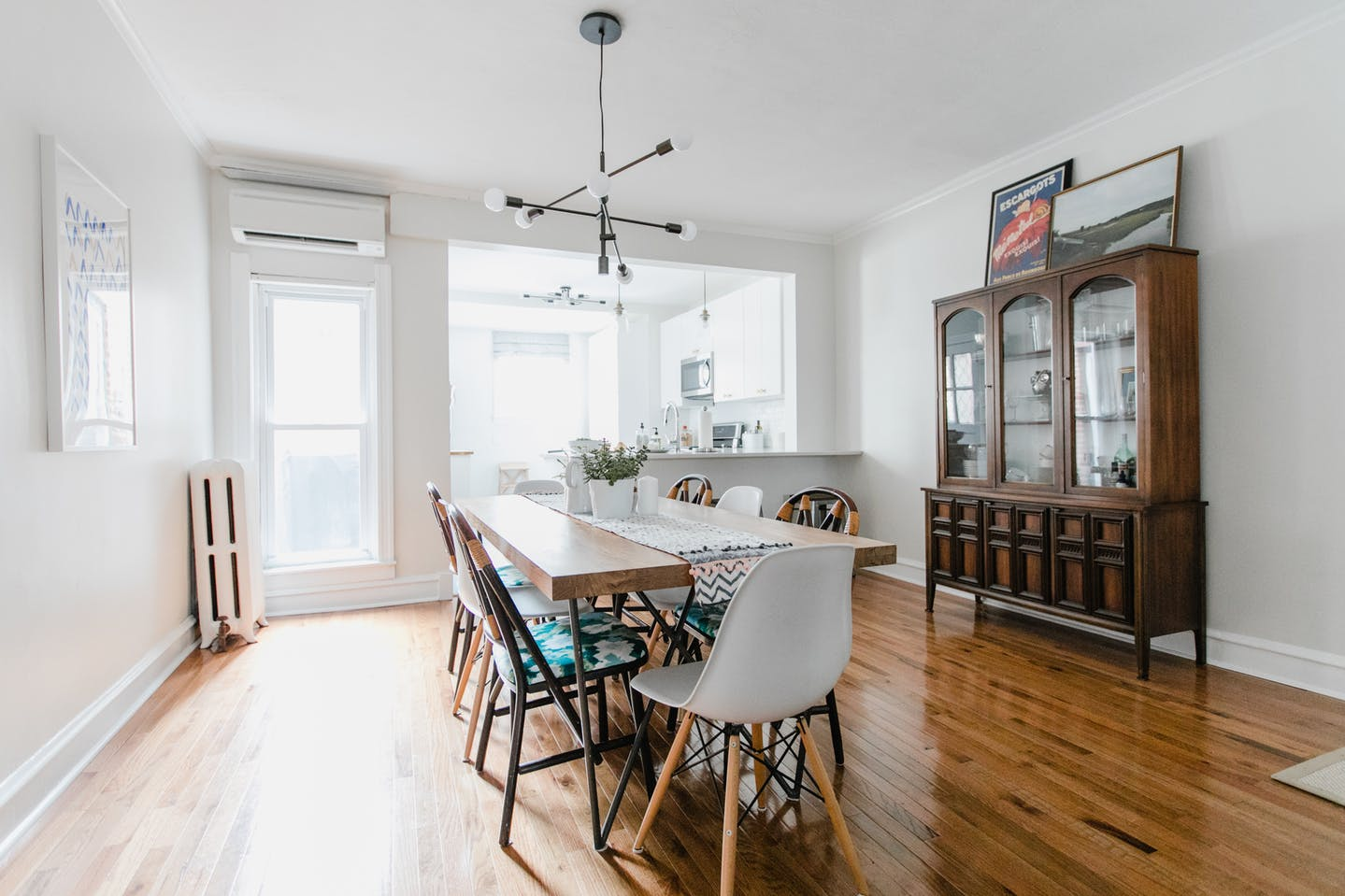 See Mix & Match Design Company's eclectic modern house tour on Apartment Therapy! Here is her dining room that opens into the white kitchen. | Mid-century china cabinet, mix and match dining chairs, West Elm light fixture.