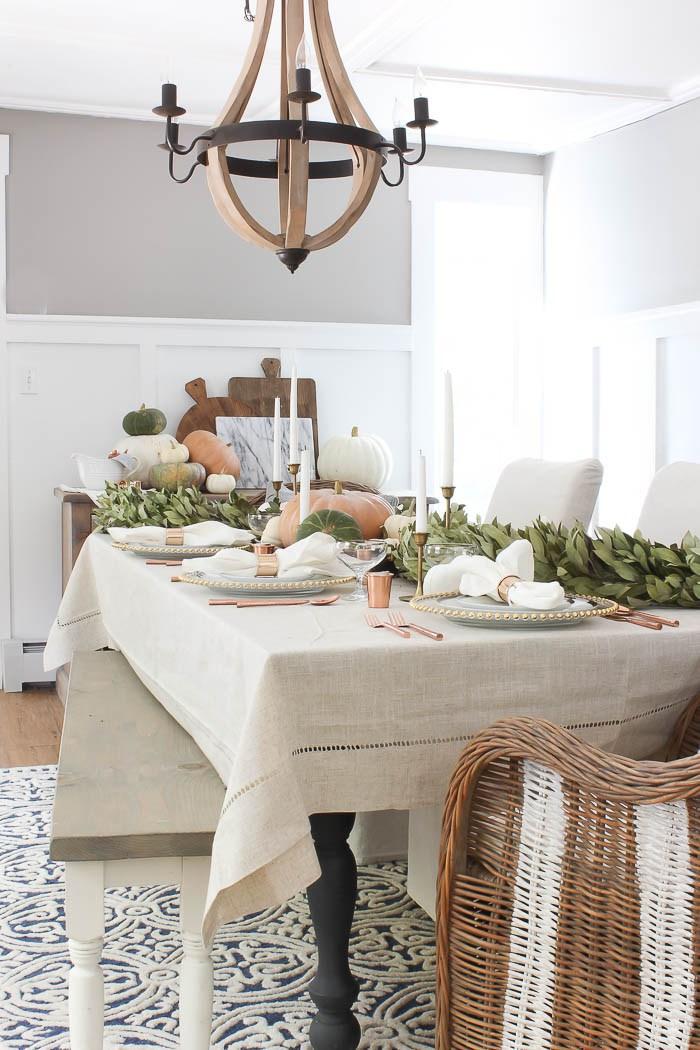 Thanksgiving tablescape inspiration: linen tablecloth, brass candlesticks, pumpkin centerpiece, greenery garland. Find more inspiring table decor ideas in this blog post!