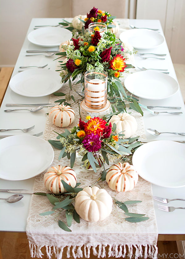 The centerpiece is the shining star in this fall tablescape. Small arrangements of flowers in fall colors flanked by greenery and pumpkins make for a beautiful and modern look. See more ideas for your fall or Thanksgiving table in this post!
