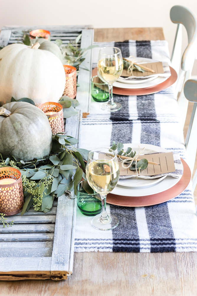 Fall/Thanksgiving tablescape ideas. Use buffalo check placemats, copper touches, and natural elements to create this table. For more ideas, head to this post!