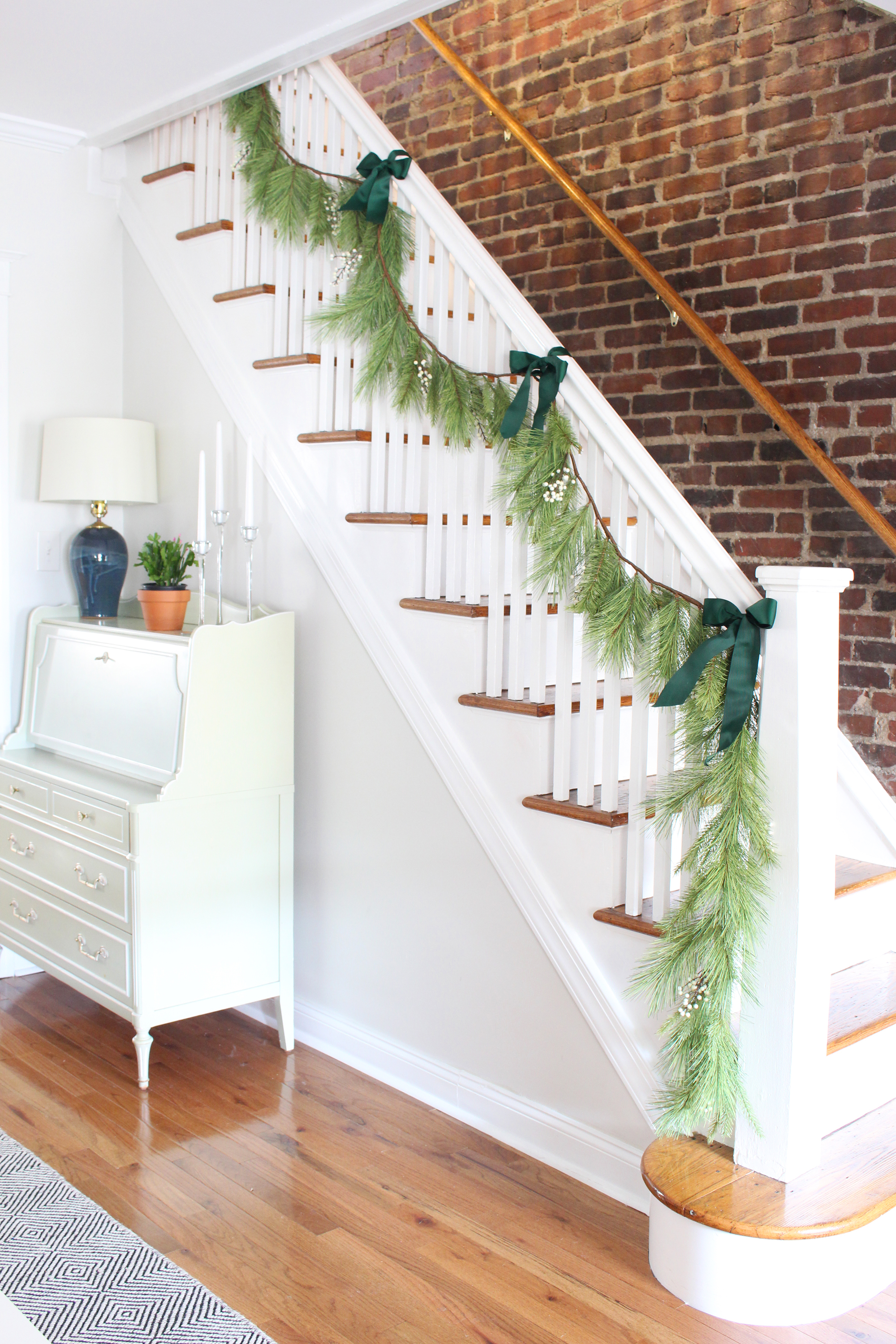 Hang artificial or real garland on your stair railing as Christmas decor. For more simple holiday decorating ideas, head to the Mix & Match blog!// simple Christmas decor, simple holiday decor, minimalist Christmas decorations