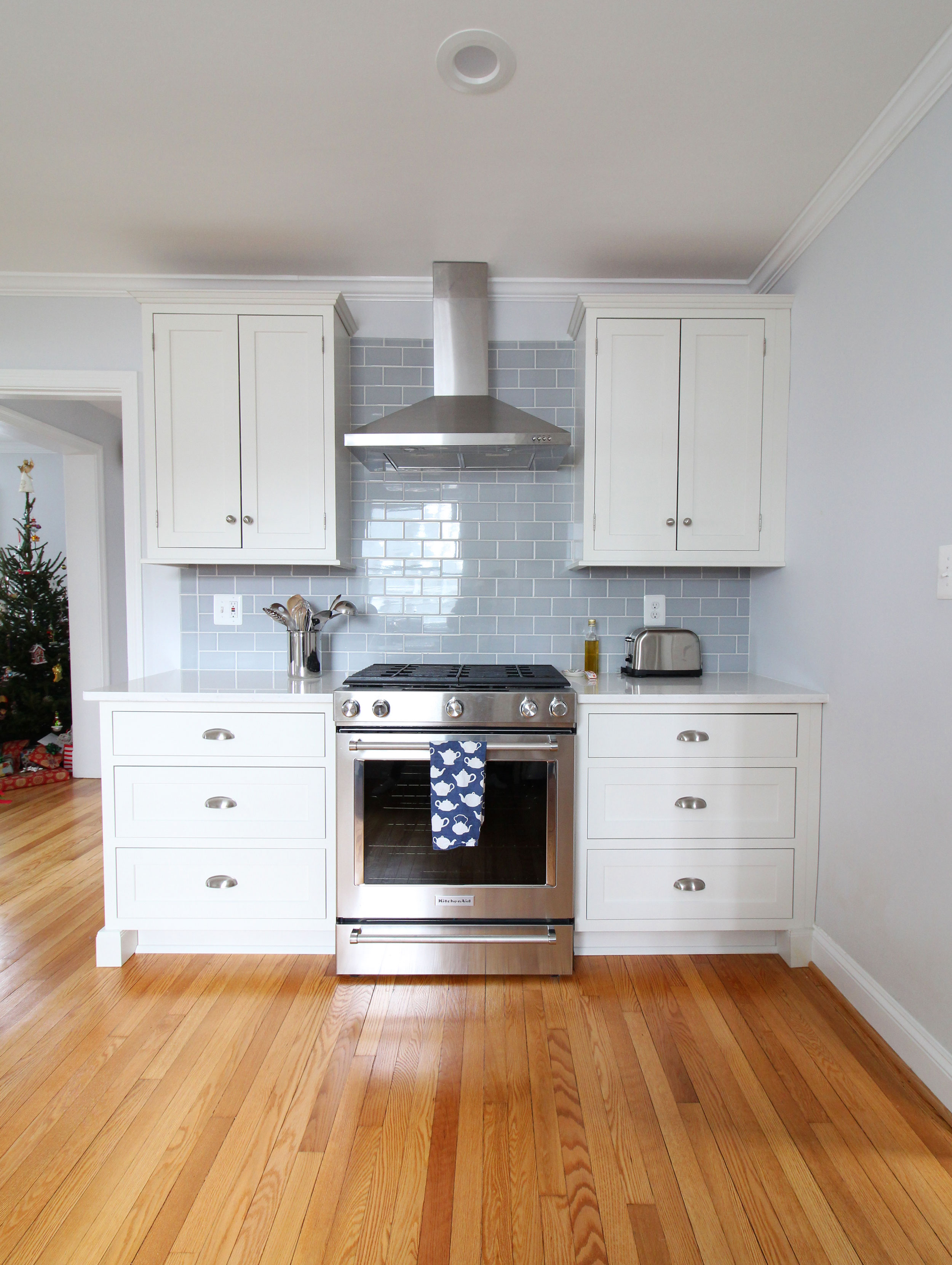 A stunning transitional farmhouse style white kitchen with inset cabinets opens up to the living room in this Virginia home. The range wall with blue glass subway tile is clean and fresh. You won't believe what this looked like before!