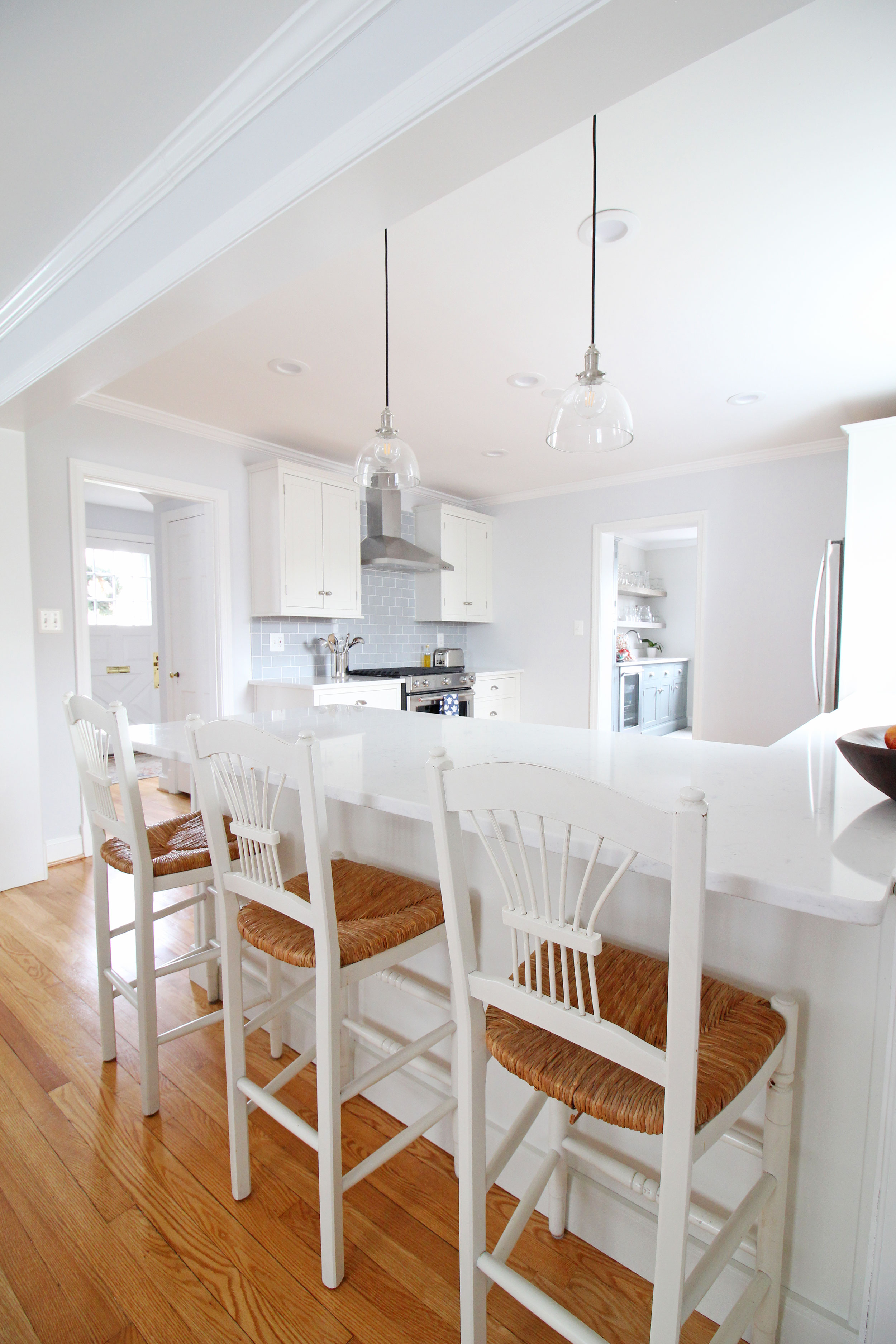 A stunning transitional farmhouse style white kitchen with inset cabinets opens up to the living room in this Virginia home. A peninsula provides great seating and a casual alternative to eating in the dining room. You won't believe what this looked like before!