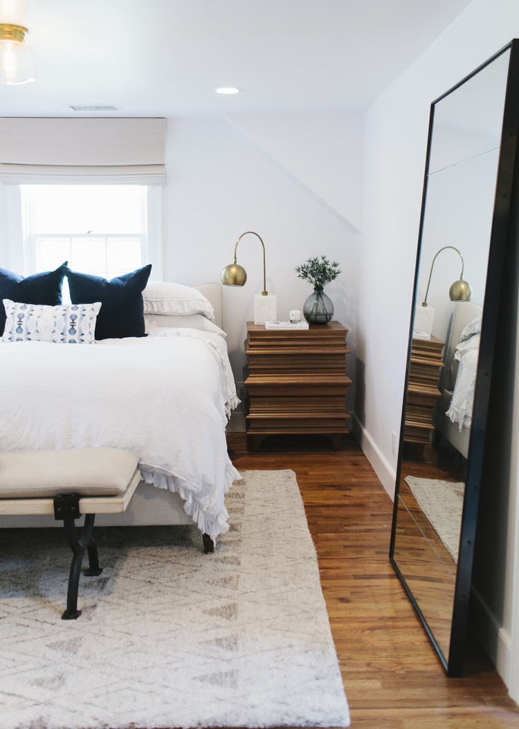 Beautiful mid-century modern meets Scandinavian bedroom with neutral colors and natural wood details.