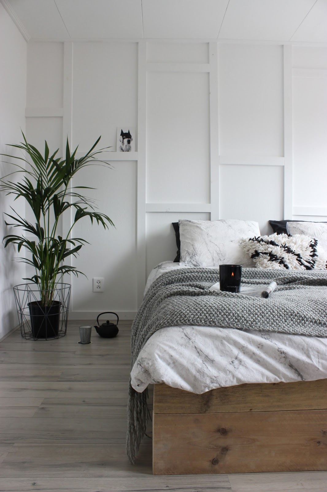 This simple, minimalist bedroom has a modern Scandinavian look with its neutral colors, cozy textures, and wall trim details.