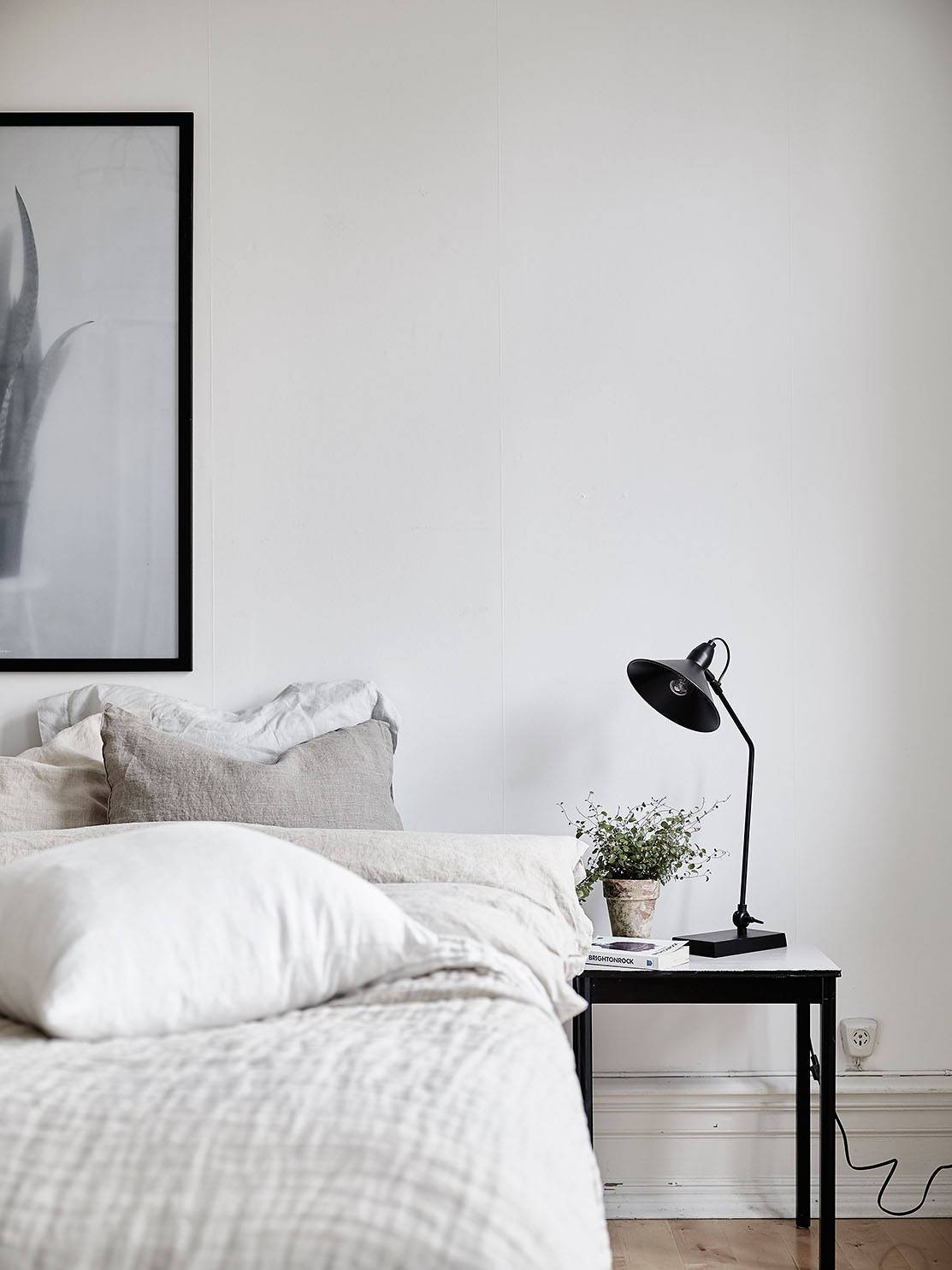 A cozy neutral bedroom with linen bedding and modern furniture. It has a lovely minimalist Scandinavian vibe going on!