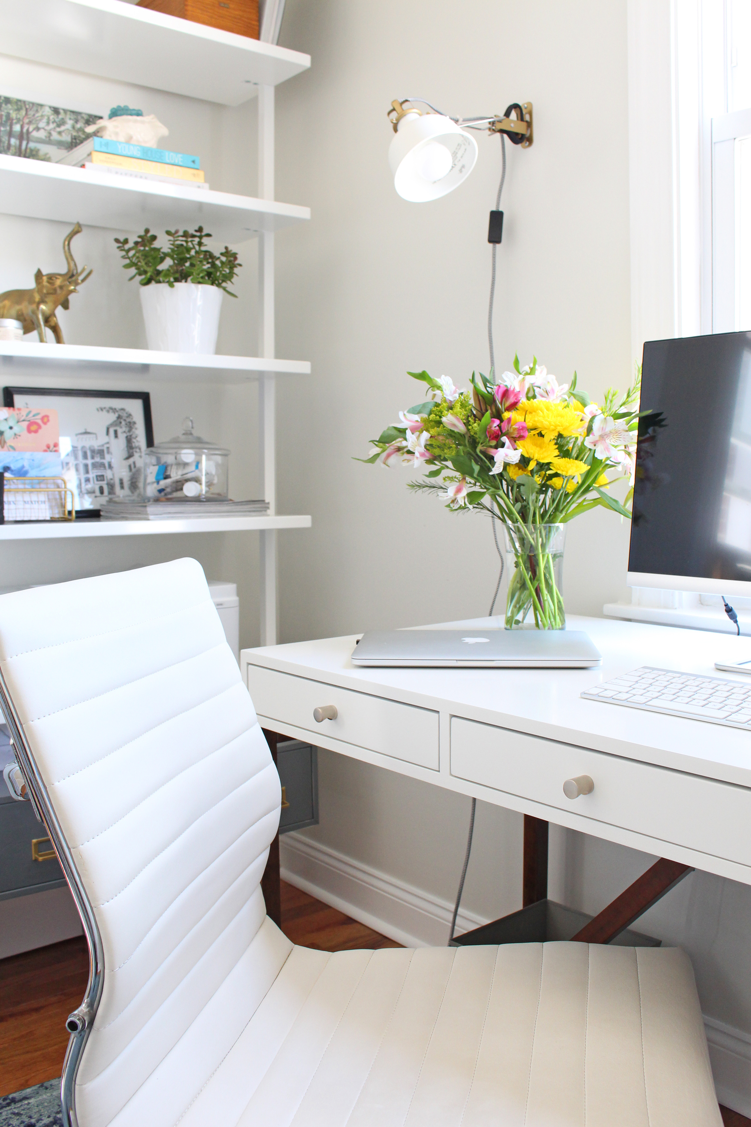The light and bright home office of an interior designer has a white desk and an overdyed blue rug, as well as open bookshelves for storage.