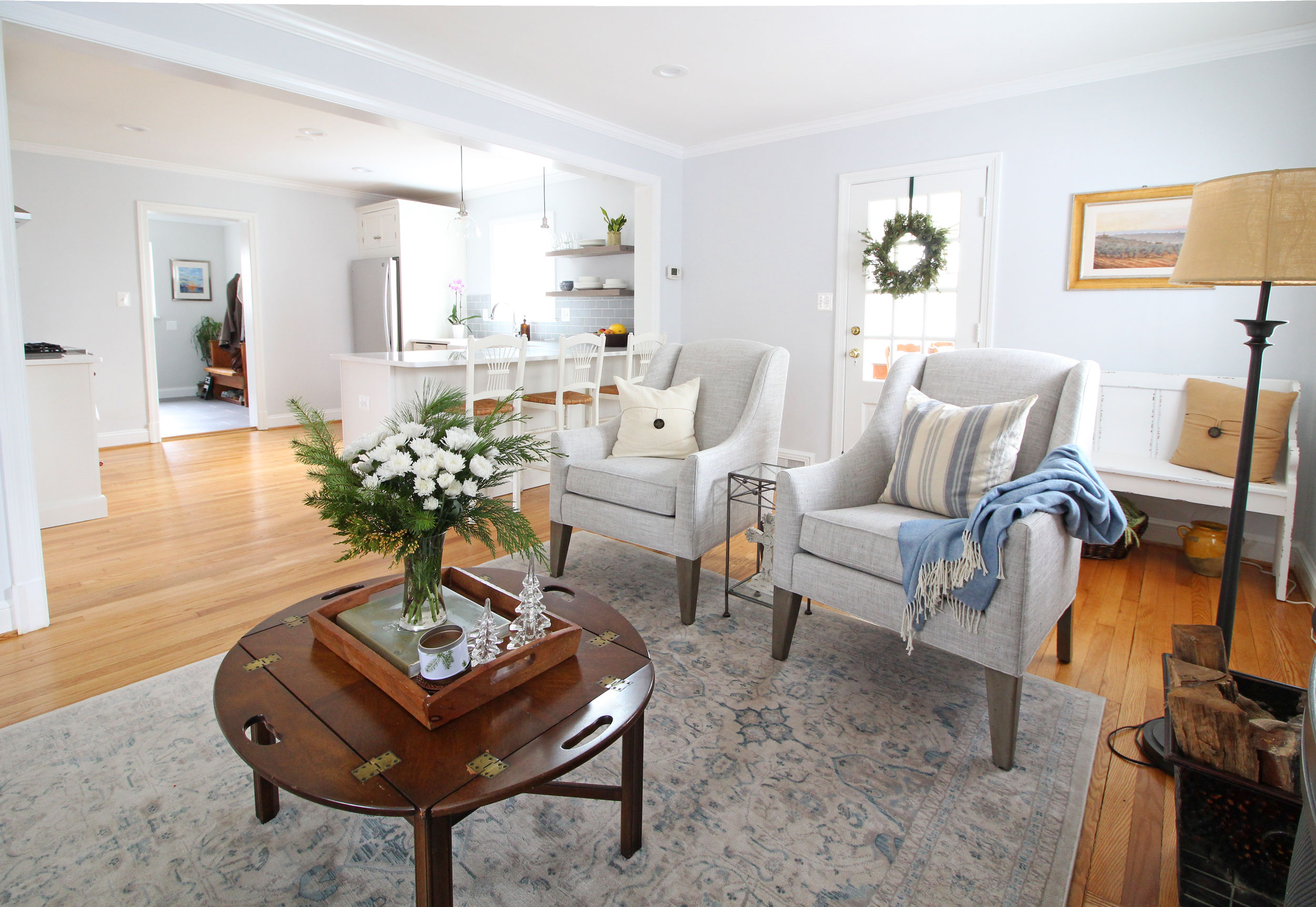 A bright and airy transitional farmhouse living room that opens up into the white kitchen.