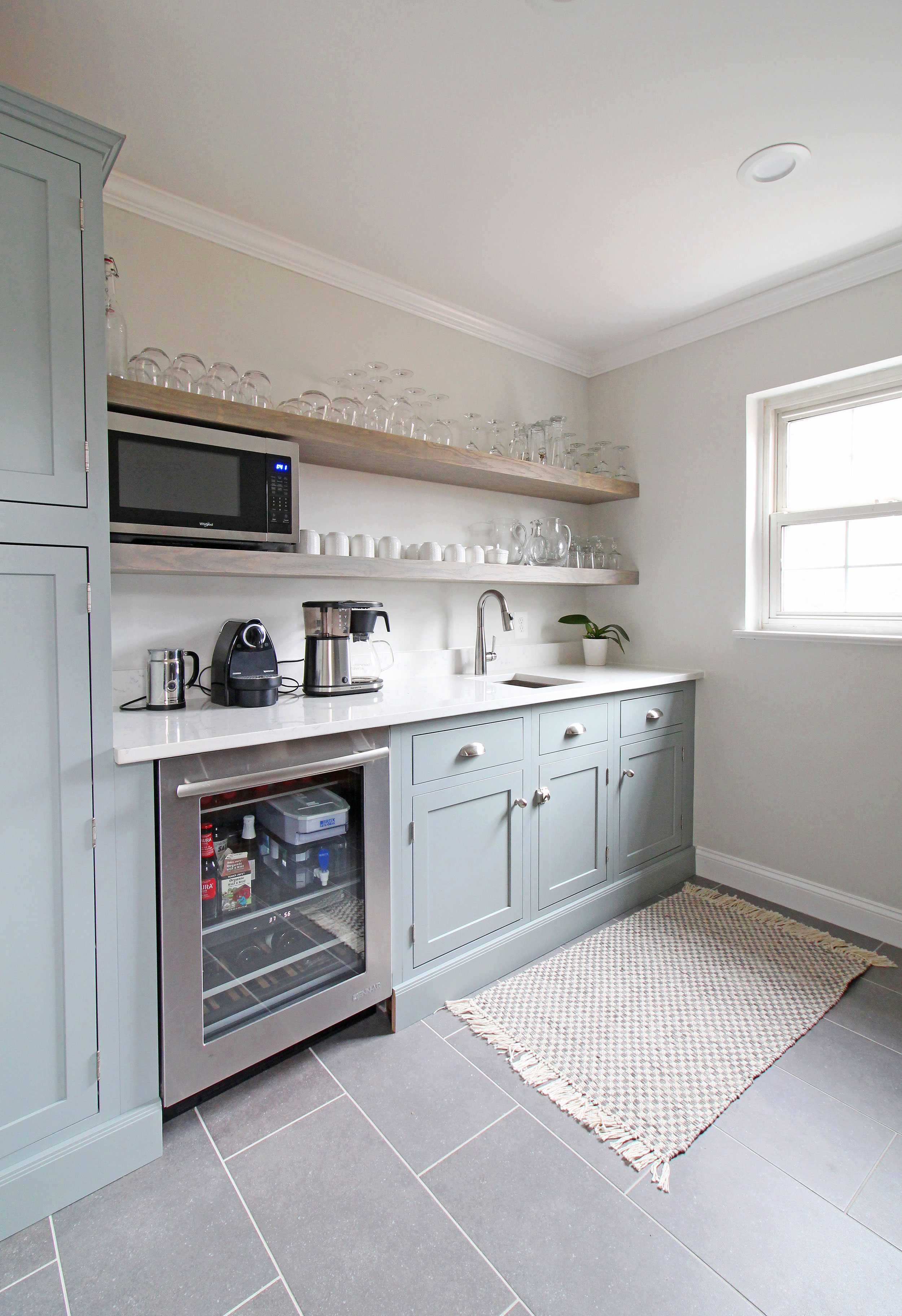The blue cabinets and open shelving in this butler's pantry provide extra storage as well as a prep area that's adjacent to a white kitchen.