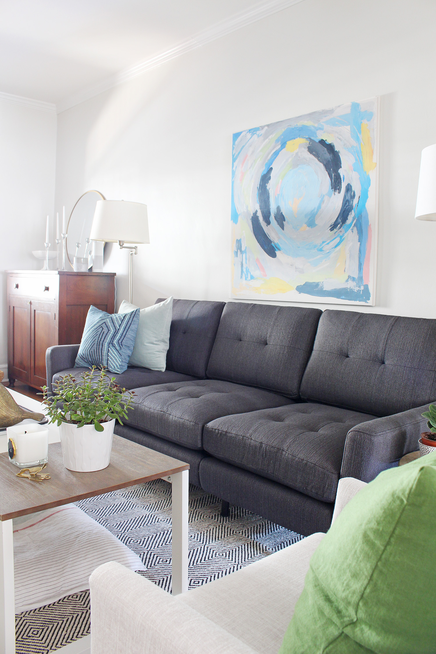A mid-century modern eclectic living room mixes new and old to create a cozy space. The neutral charcoal gray sofa has pops of color thanks to the blue throw pillows.