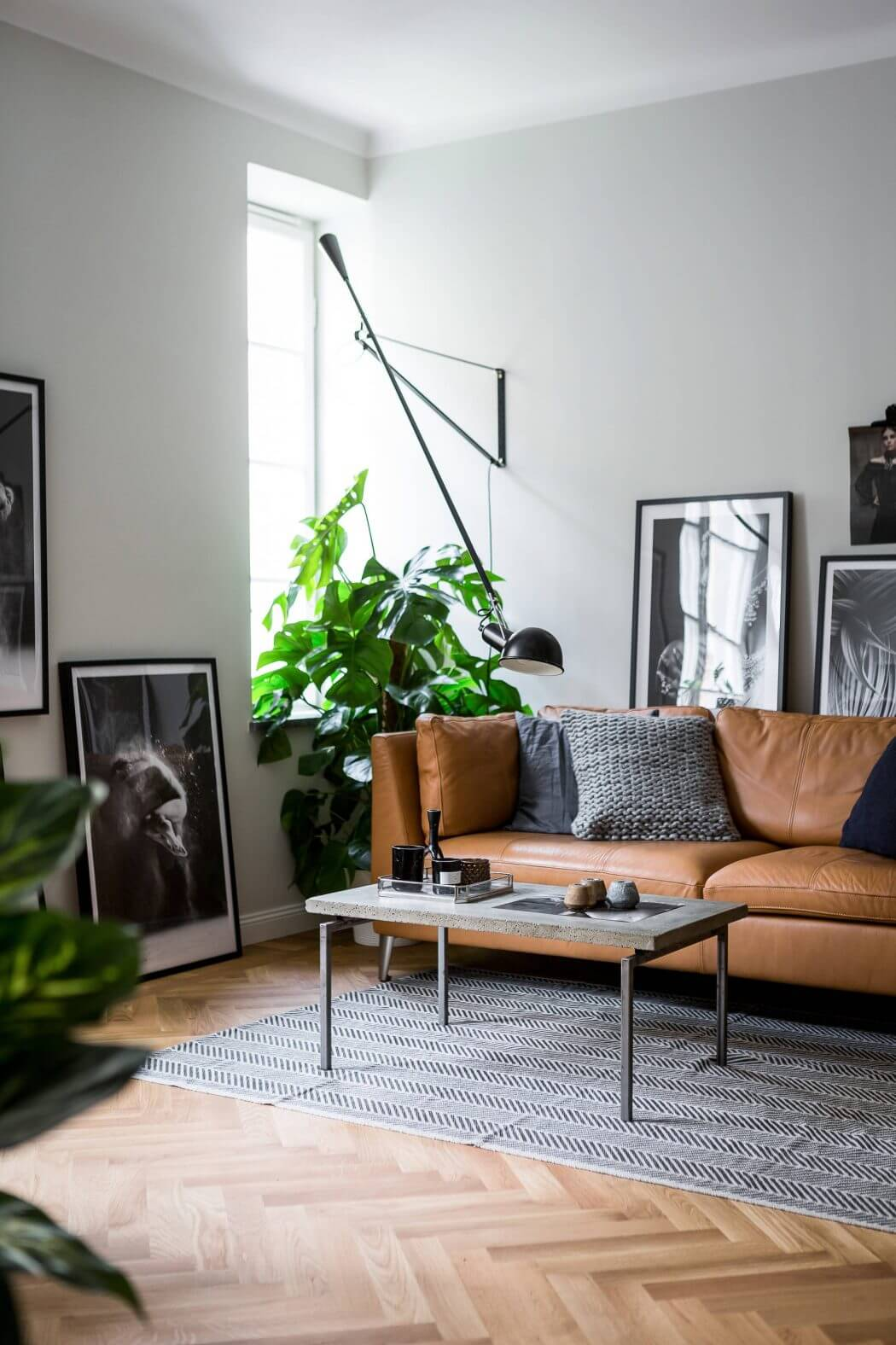 Love the look of this moody masculine living room with its simple Scandinavian style? A cozy leather sofa, simple accessories, and a modern light fixture work together beautifully. Get the look of this style on the Mix & Match Blog!