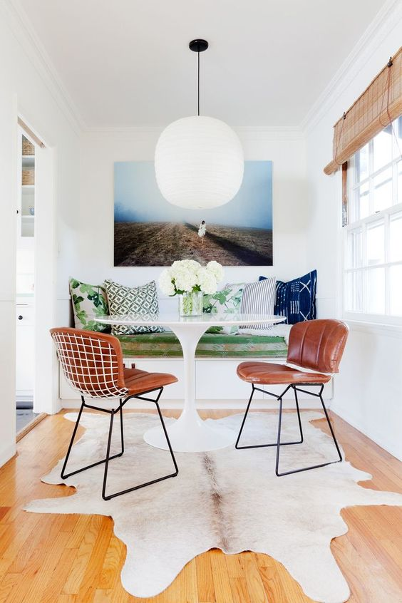 Get the look of this small, colorful modern breakfast nook with its green pillows, white pedestal table, and modern leather chairs over on the blog!