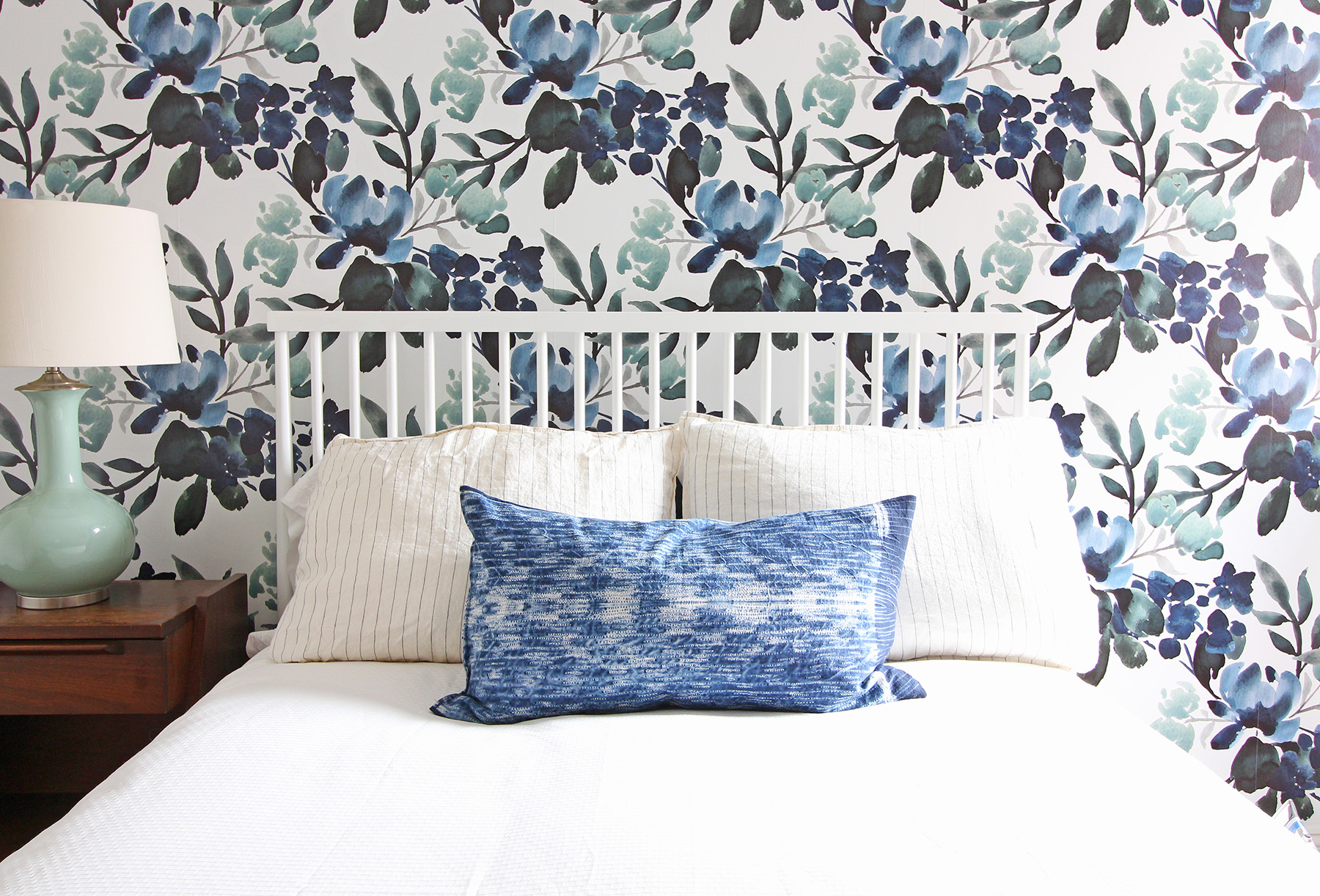 An indigo lumbar pillow is a great accent to this bold blue and green floral wallpaper in a modern farmhouse eclectic guest bedroom.