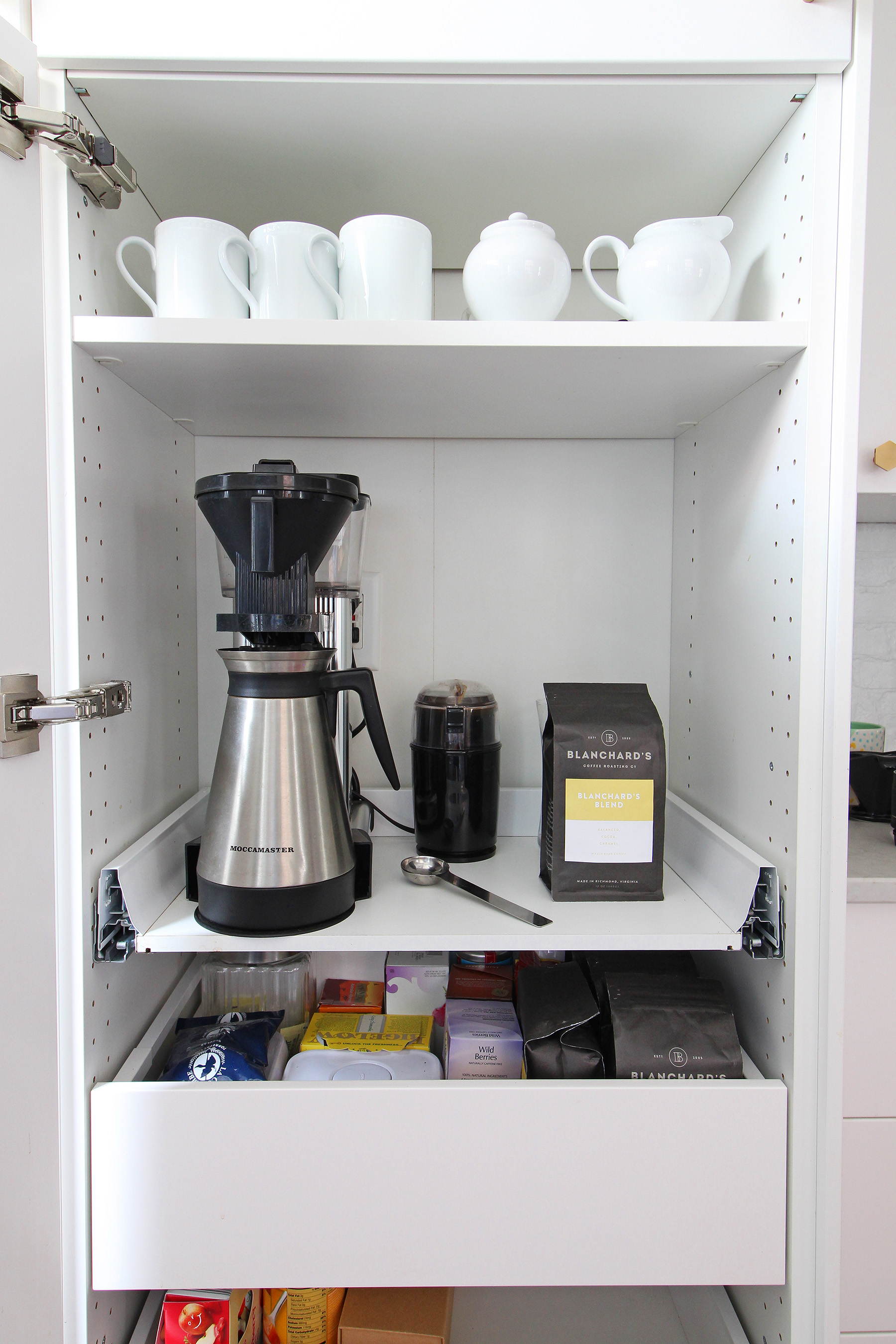 Read my review of our modern white kitchen renovation using IKEA cabinets, Caesarstone countertops, and gray tile floors two years after we renovated. We love our coffee station that's hiding in our tall pantry. You can pull out the drawer to add water and brew without worrying about it steaming up!
