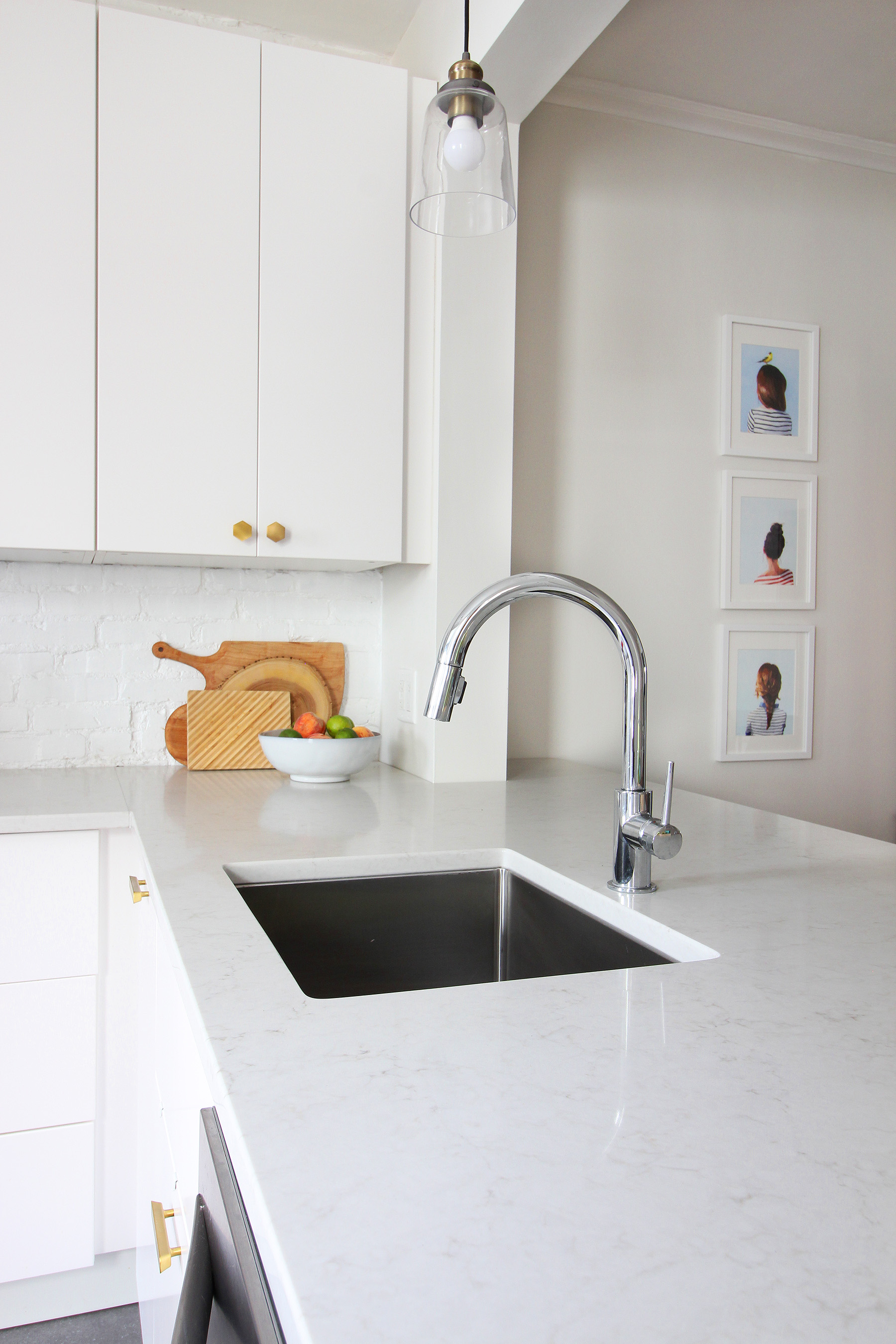 Read my review of our modern white kitchen renovation using IKEA cabinets, Caesarstone countertops, and gray tile floors two years after we renovated.