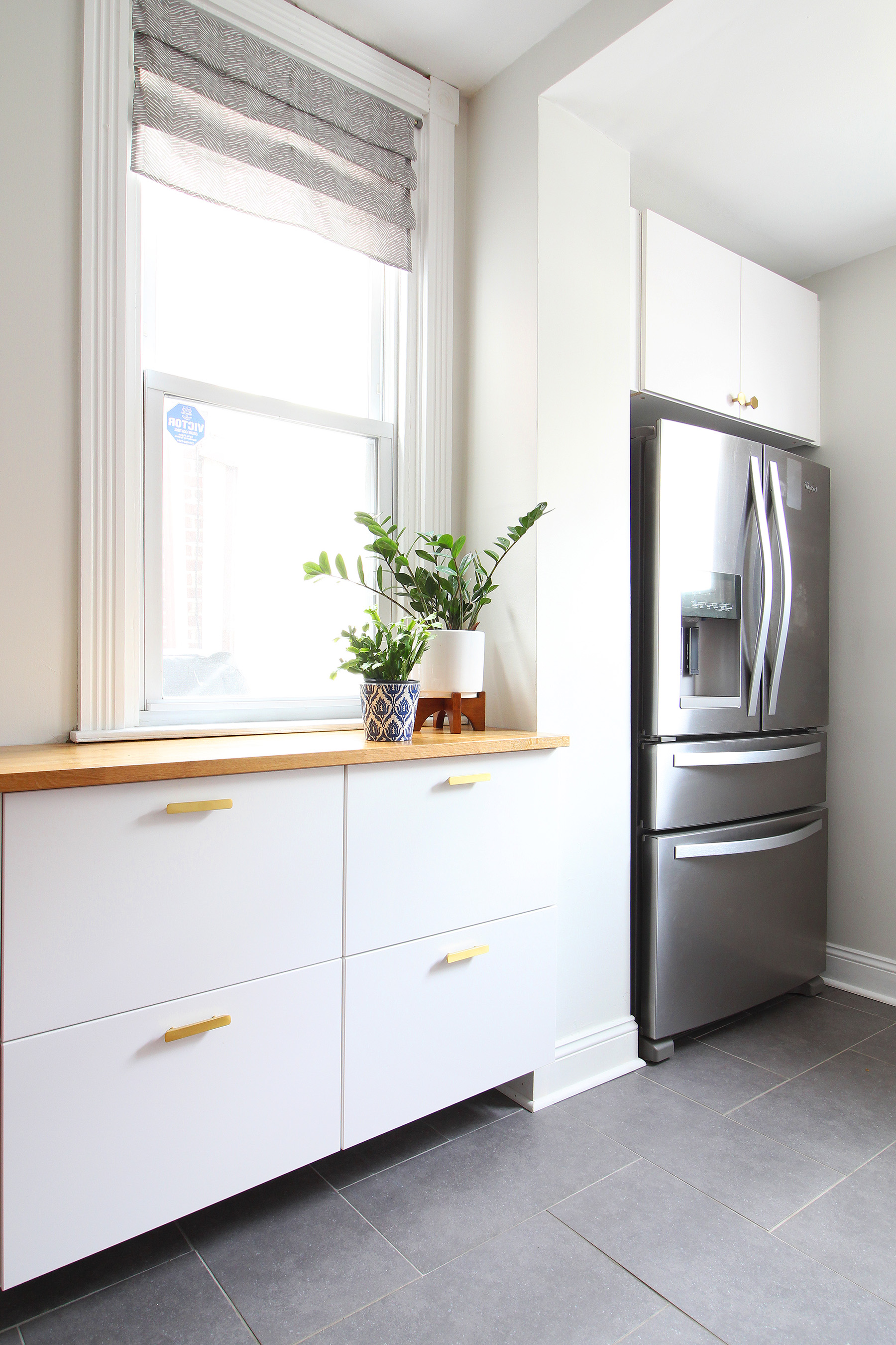 Read my review of our modern white kitchen renovation using IKEA cabinets, Caesarstone countertops, and gray tile floors two years after we renovated. We added radiant heat underneath our tile floors and it is the BEST thing in the winter!