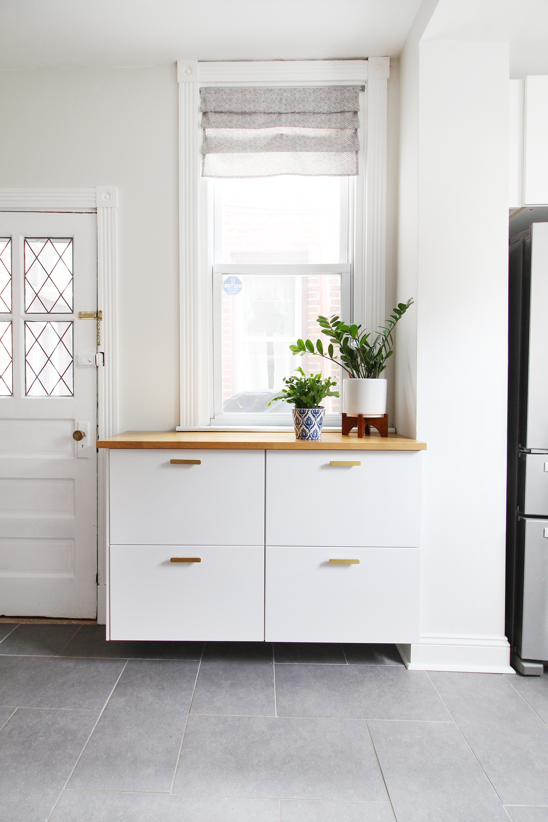 Read my review of our modern white kitchen renovation using IKEA cabinets, Caesarstone countertops, and gray tile floors two years after we renovated. We installed butcher block on this floating cabinet run and it's still going strong!