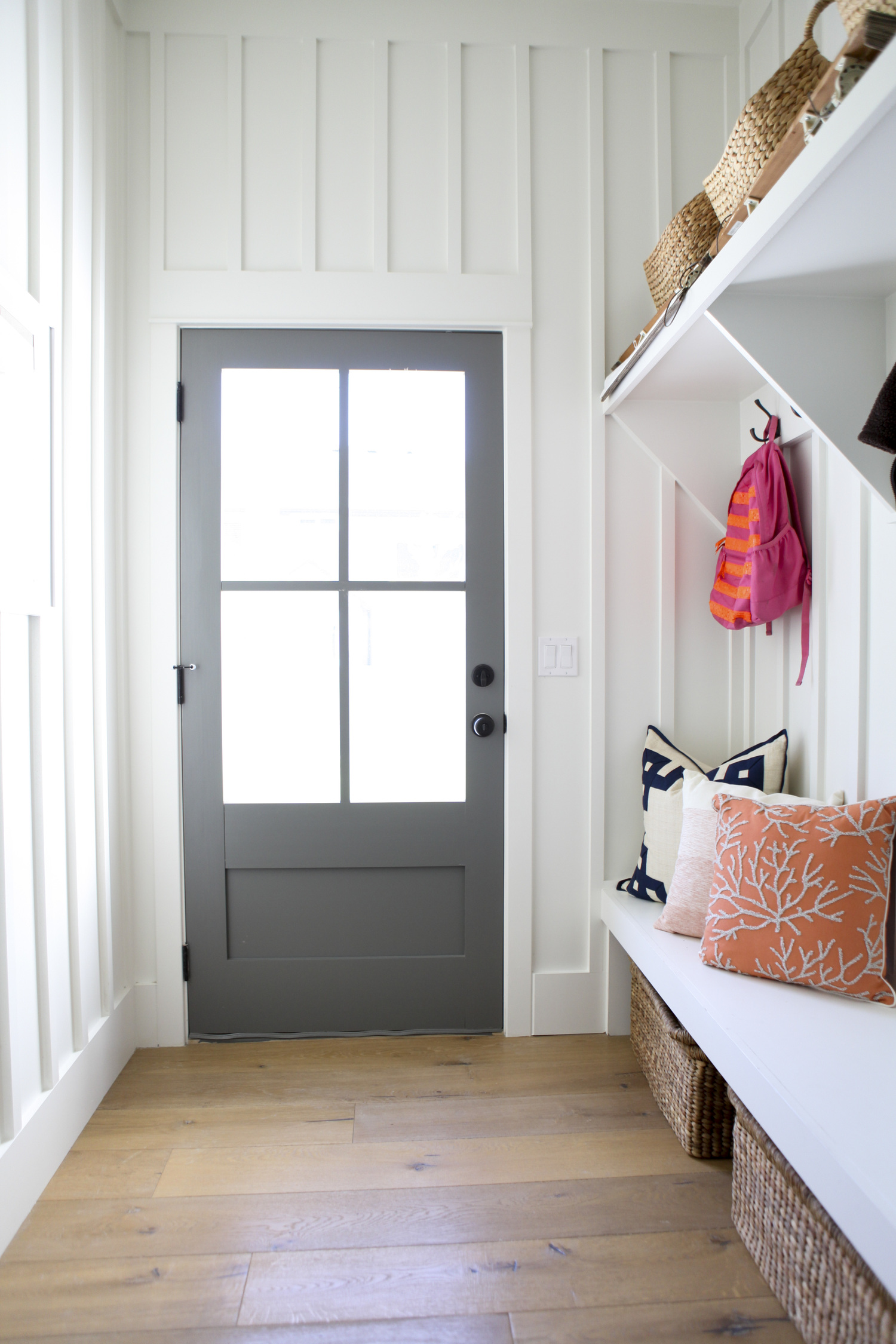 A built-in bench in this entryway/mudroom makes for a great drop zone and storage area. I also love that gray door.For more ways to use benches in your home, be sure to head to the blog post!