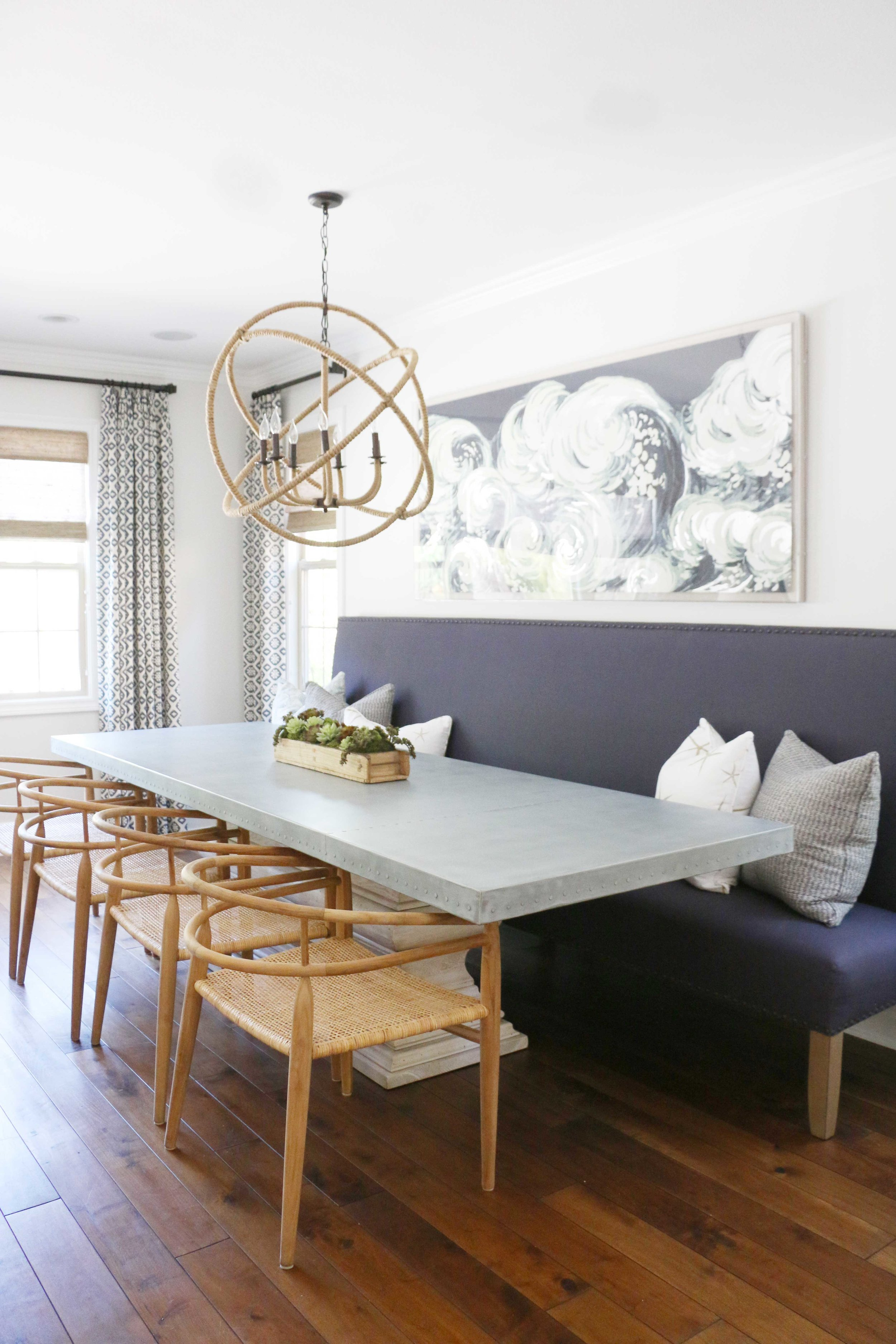 A built-in upholstered dining bench is great for extra seating and maximizes space in this coastal home. For more ideas on how to use benches in your home, head to this blog post!