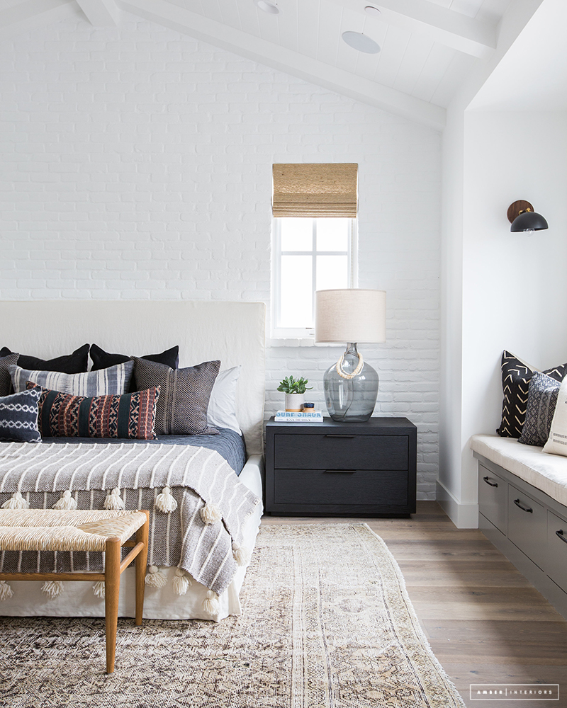 A woven bench fits in perfectly at the end of the bed in this coastal modern California home. For more ideas on how to use benches in your home, head to the blog post!