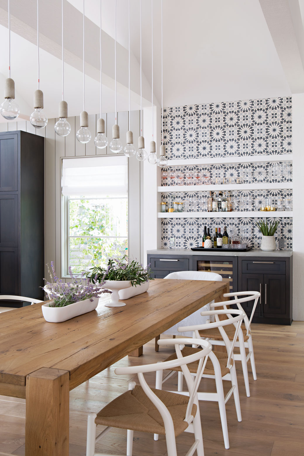 Inspiration for a coastal modern dining room. This blue and white color palette with those white wishbone chairs feels so fresh. I'm also digging the tiled backsplash, dark cabinets, and white floating shelves. Find out how you can get a similar look in your own home on the blog!