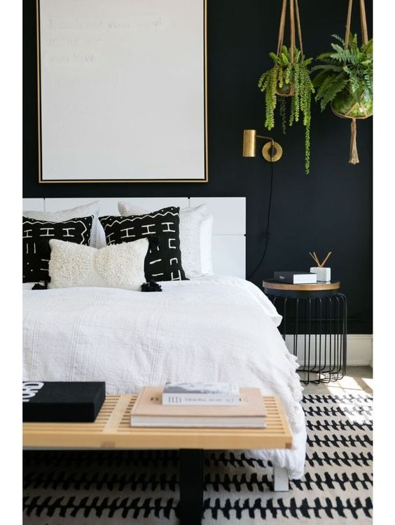 Love the look of this black and white bedroom with a modern eclectic style. Those hanging plants in the corner and black mudcloth pillows are great details. See how you can get a similar look in your own home over on the blog!