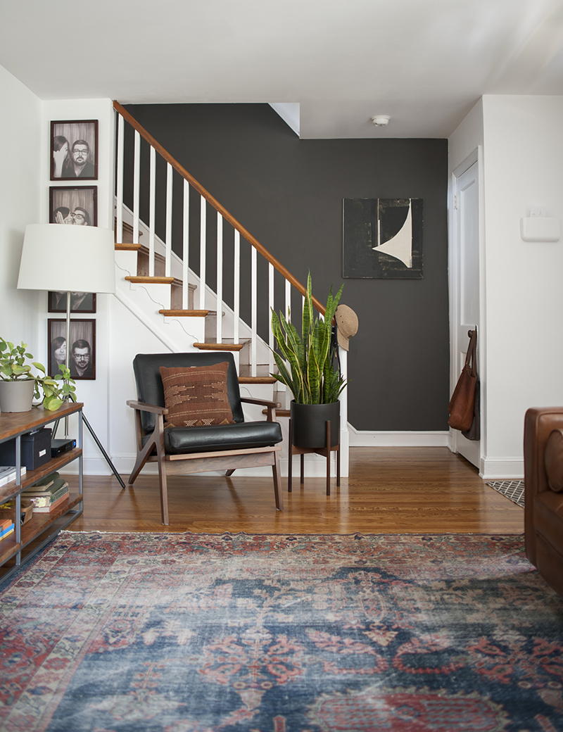 This mid-century modern eclectic living room has a warm and cozy feeling with its vintage rug, mid-century chair, and dark stairwell wall. Like this decorating style? Head to the Mix & Match blog to see how you can create a similar look in your own home!