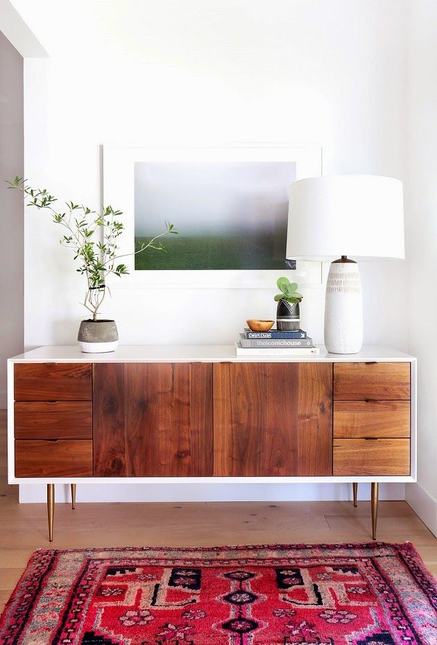 This mid-century modern eclectic bedroom has a warm and cozy feeling with its vintage rug, mid-century credenza, and landscape artwork. Like this decorating style? Head to the Mix & Match blog to see how you can create a similar look in your own home!