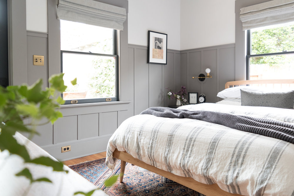 Need help picking out window treatments? I've got you covered! This simple, but thorough guide will walk you through how to choose curtains, shades, and blinds for your home. I love this gray bedroom with its board and batten walls, roman shades, and mid-century meets eclectic style.