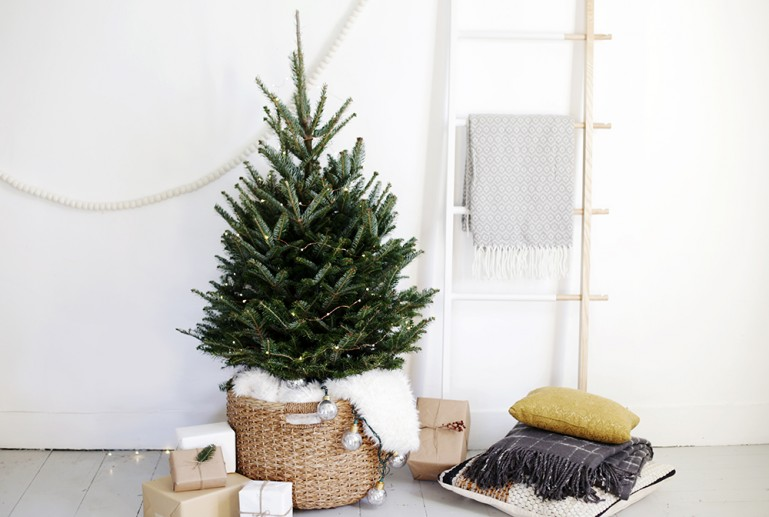 Keep your Christmas tree simple and minimalist by only adding fairy lights and use a basket as a stand. This one from The Merrythought is a perfect example! | Scandinavian Christmas decorating