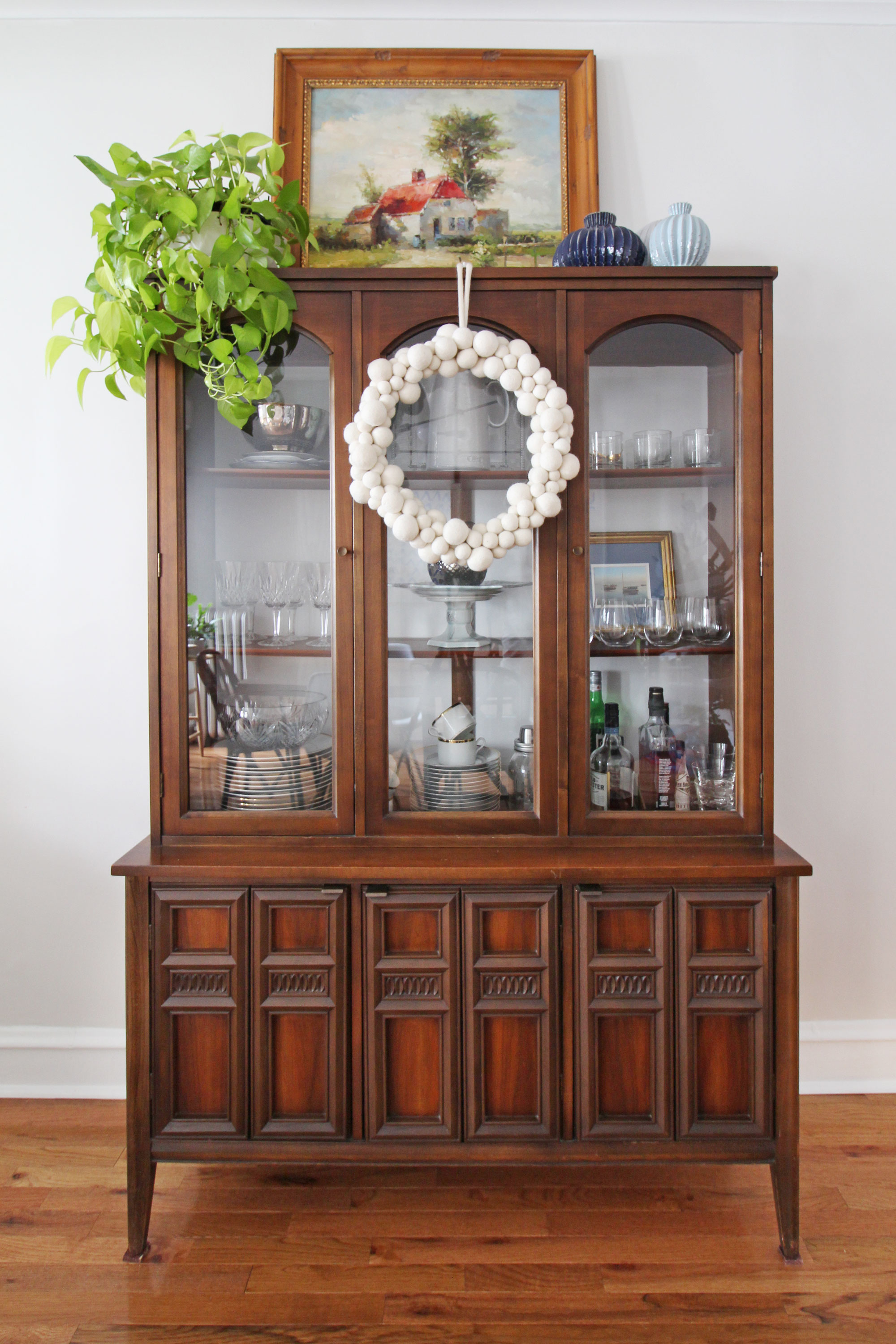 A simple way to add a little bit of Christmas cheer in your home is to hang a wreath in an unexpected place in your home. Here, I added a white felt ball wreath to our mid-century modern china cabinet. It's the perfect touch of holiday spirit for our dining room. Christmas decorating can be simple and easy!