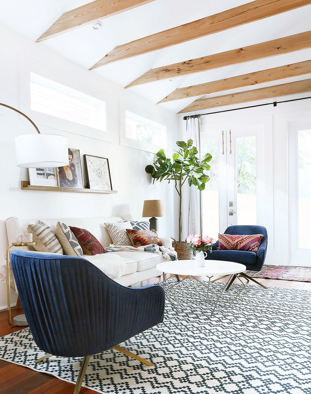 Need help with how to choose a coffee table or ottoman for your living room? I've got you covered! I'll walk you through what you need to think about when you're shopping for one for your home. Plus, I've got a roundup of my favorite coffee tables and ottomans to help you get started in your search. // Modern eclectic living room with blue swivel chairs and a round coffee table.