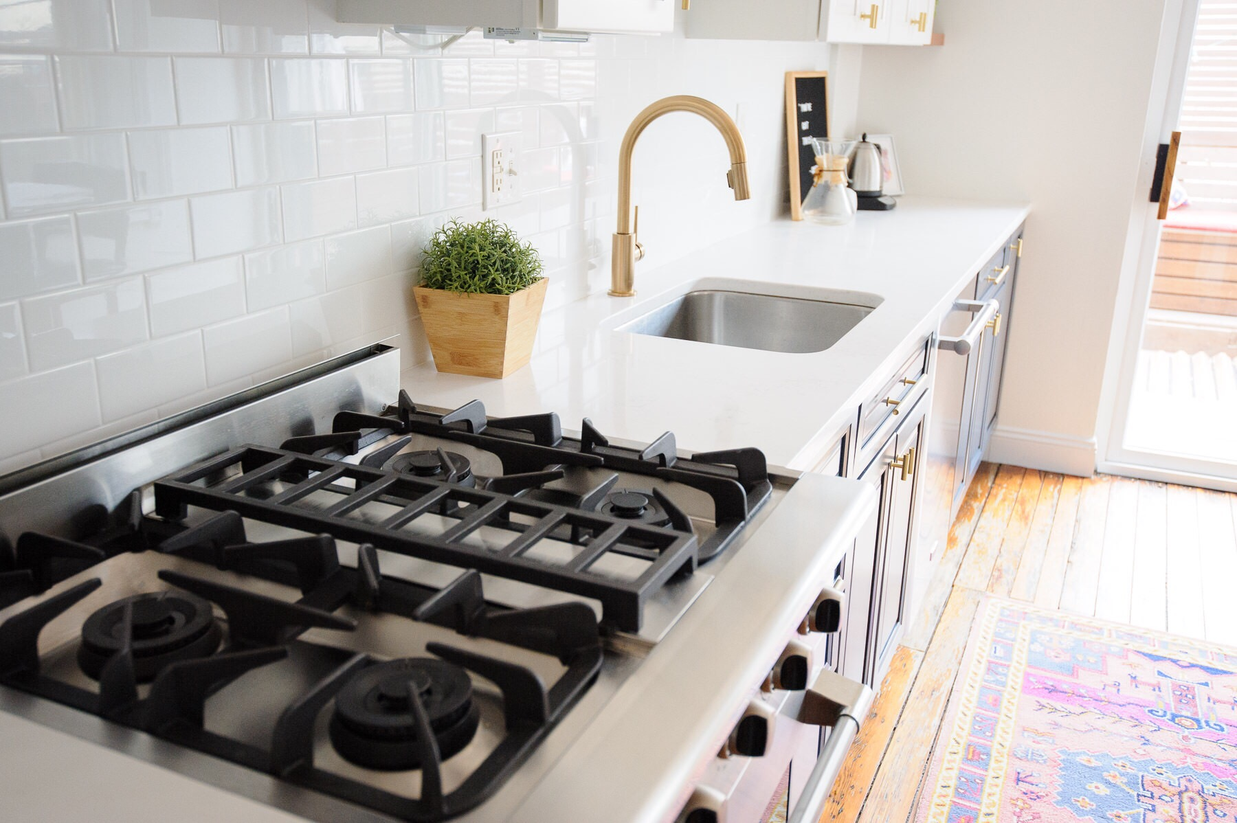 The after: a white, navy, and brass kitchen makeover in a Philadelphia row home. This kitchen got a serious refresh to give it a modern, clean, and cozy look. We chose Hale Navy for the lower cabinets, white subway tile, marble-like quartz countertops, and matte brass cabinet hardware. Designed by Mix & Match Design Company. Photos by Nate Photographic.