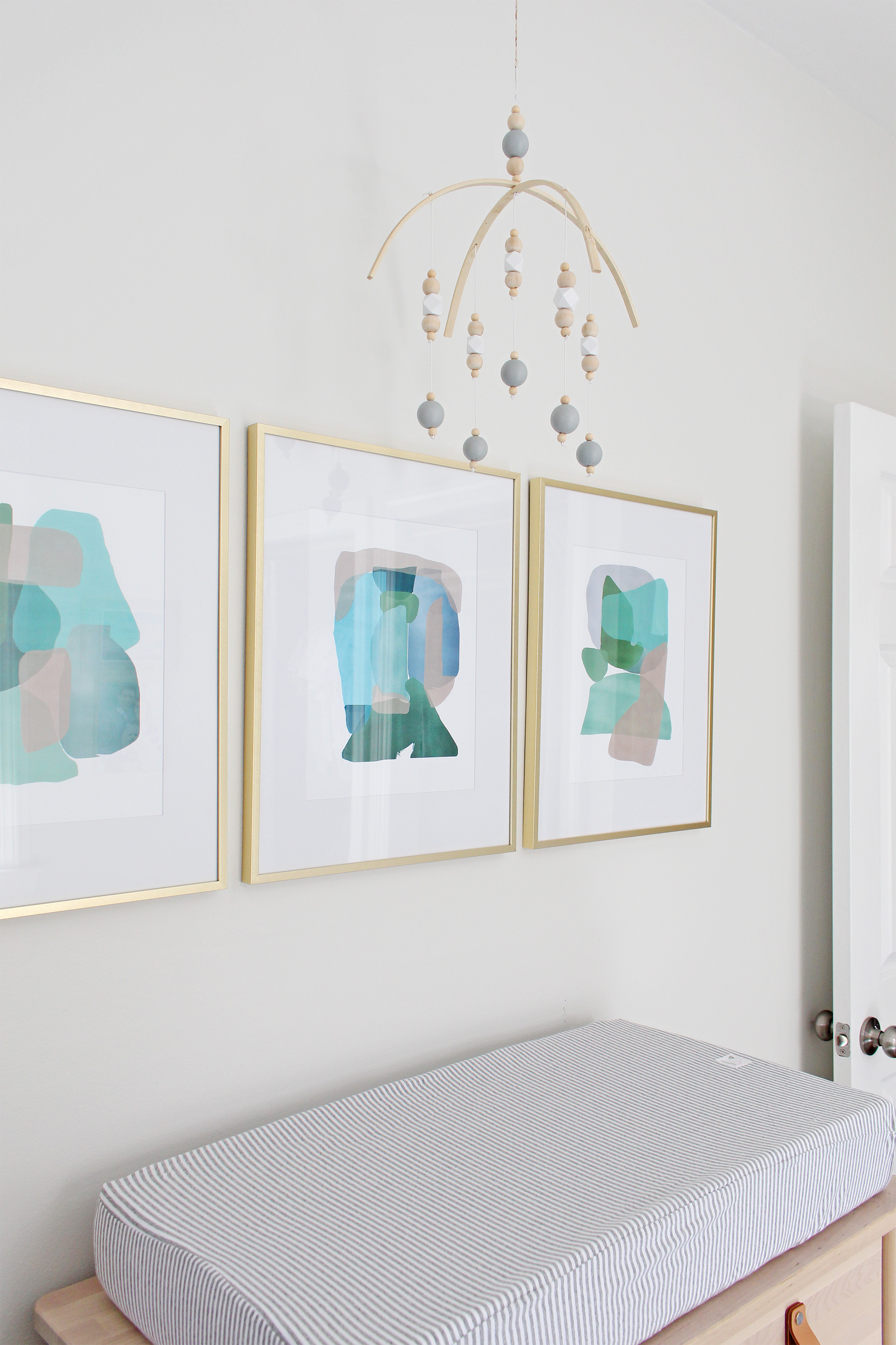 "Come on over to the Mix & Match Design Company blog for this cozy modern nursery nook reveal! This space is shared with a home office and is full of great ideas on how to squeeze in a small nursery into a closet. The ""nursery nook"" concept is perfect if you live in a smaller home. Abstract art and Scandinavian mobile."